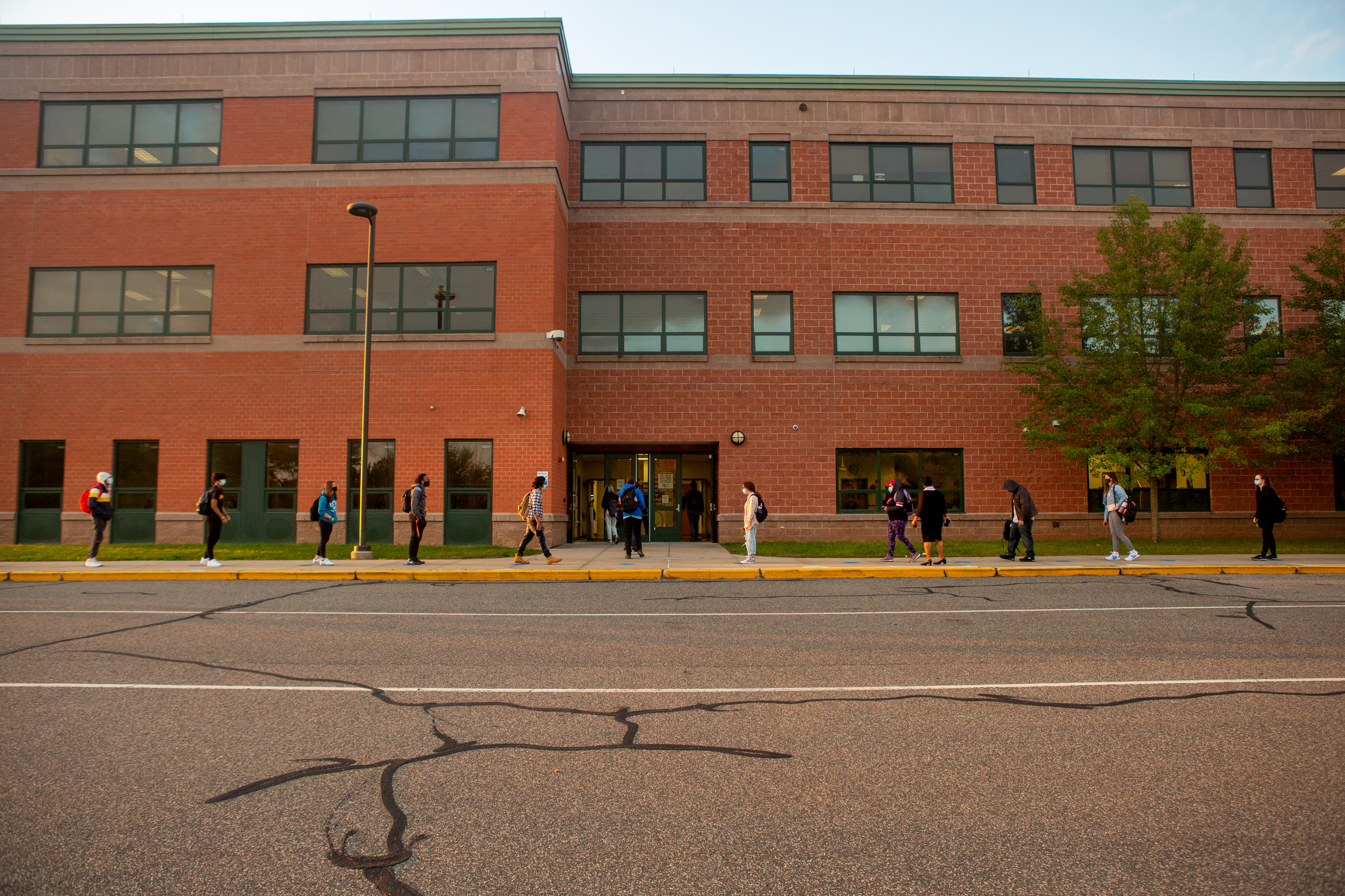 Students line up on socially distanced dots painted on the sidewalk to wait their turn to be scanned by a temperature screener before classes.