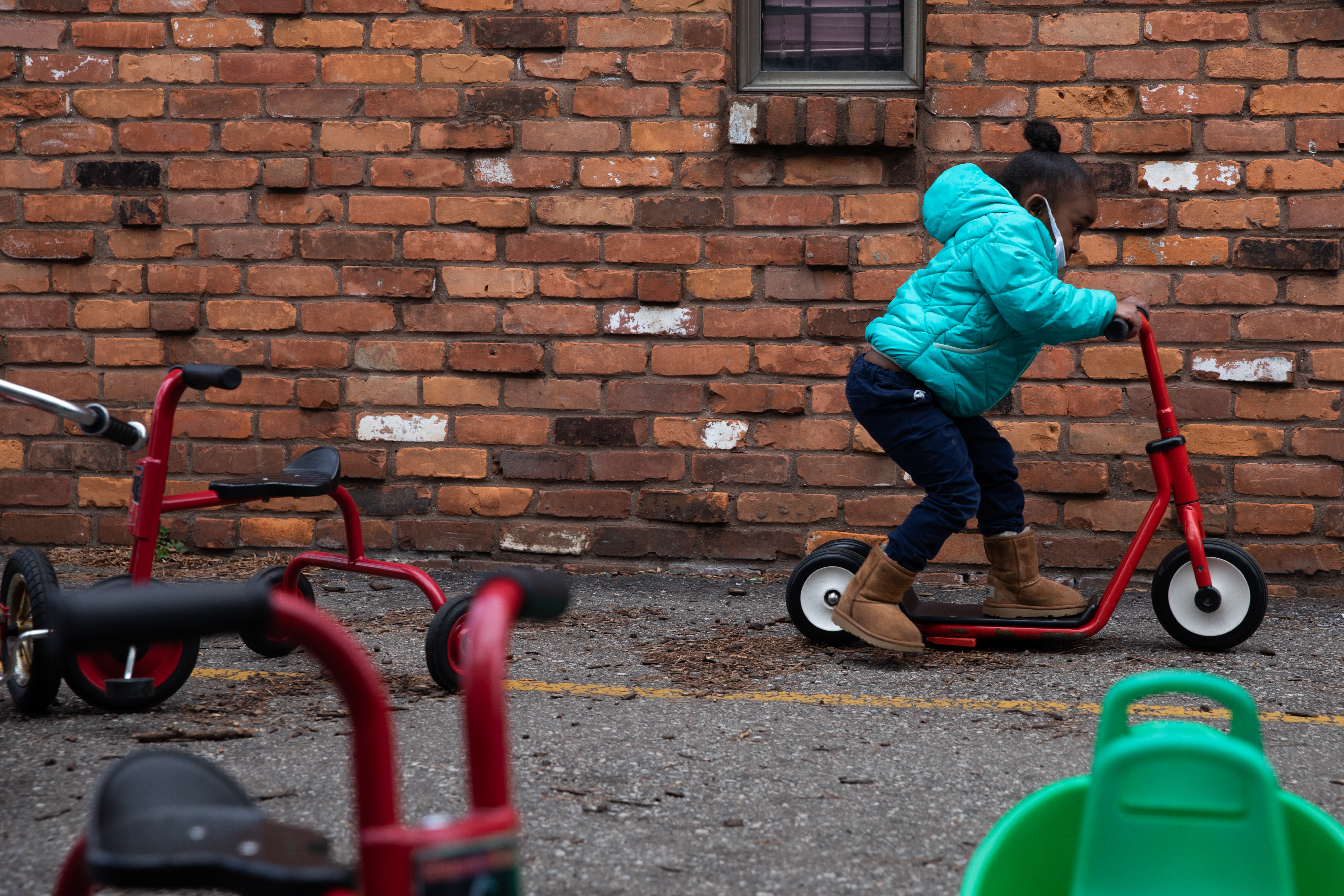 Payton Watson rides around on a scooter as the preschoolers play outside at Little Scholars child care center in Detroit, Michigan, U.S., on Thursday April 1, 2021.
