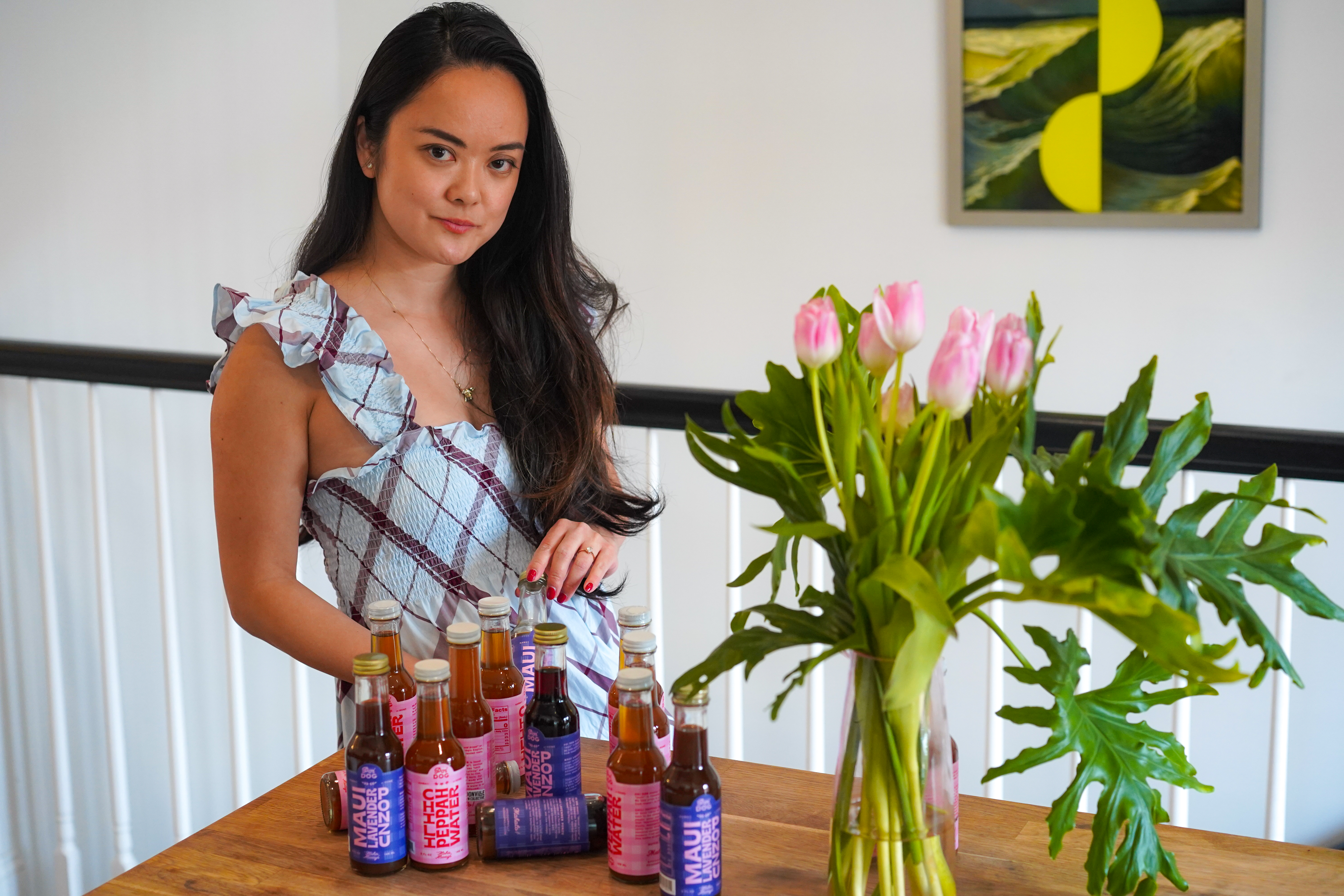 kiki aranita stands with a table of her poi dog sauces and a bunch of tulips