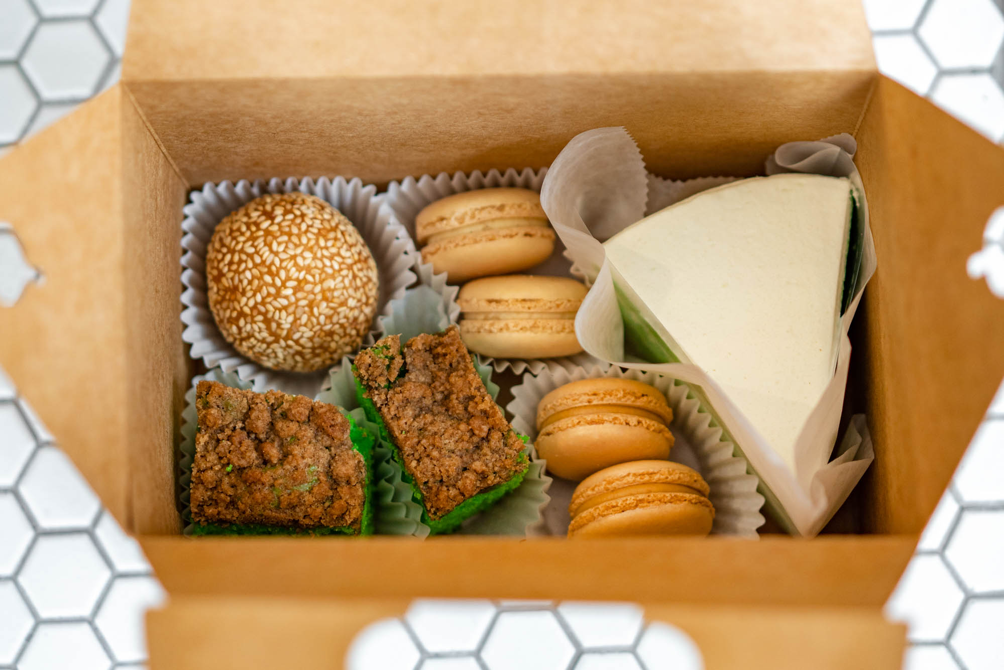 A close-up photo looking into a brown box that is filled with pastries, including a slice of white-frosted cake and four macarons