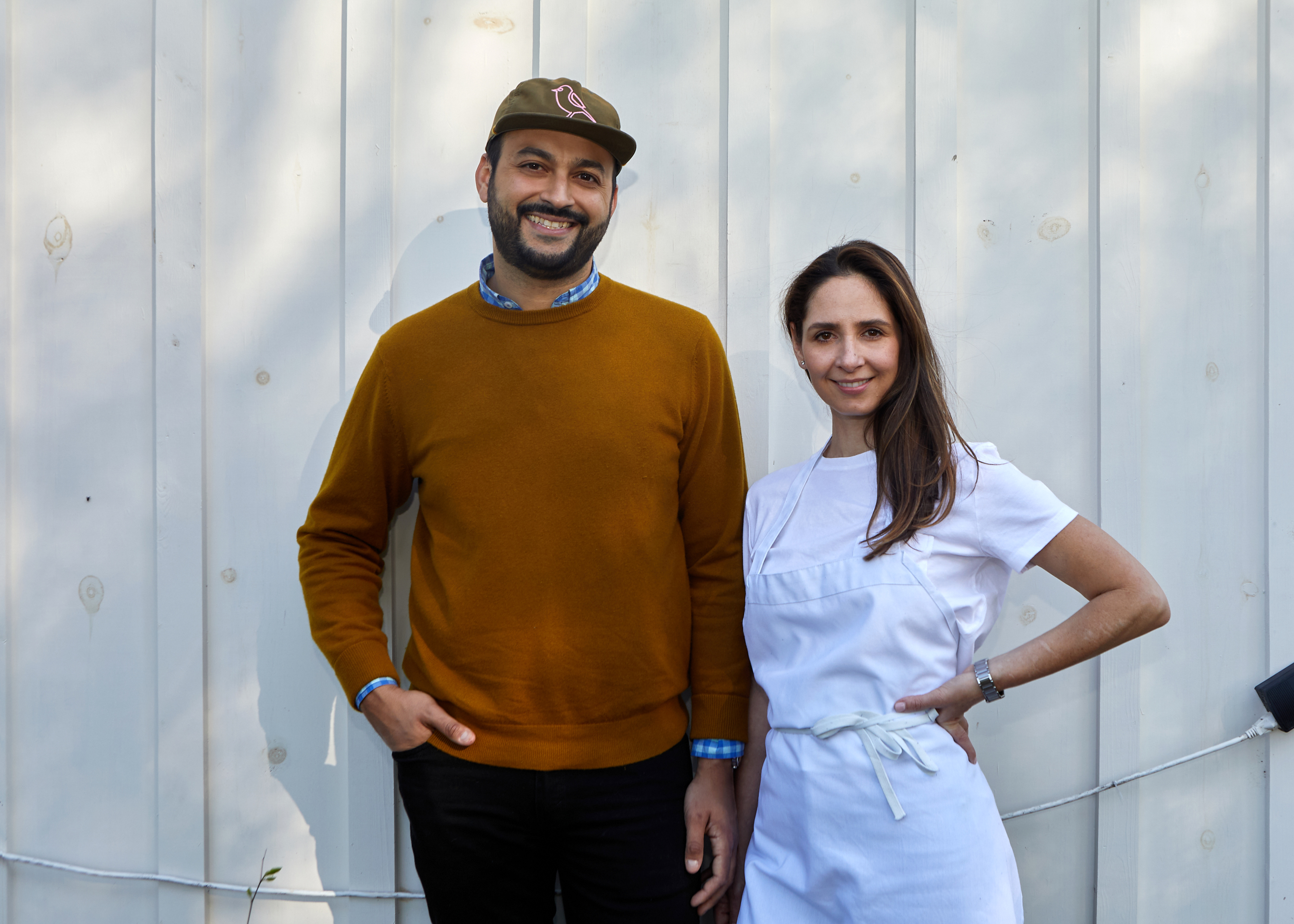 A man and a woman in a white apron standing in front of a white wall