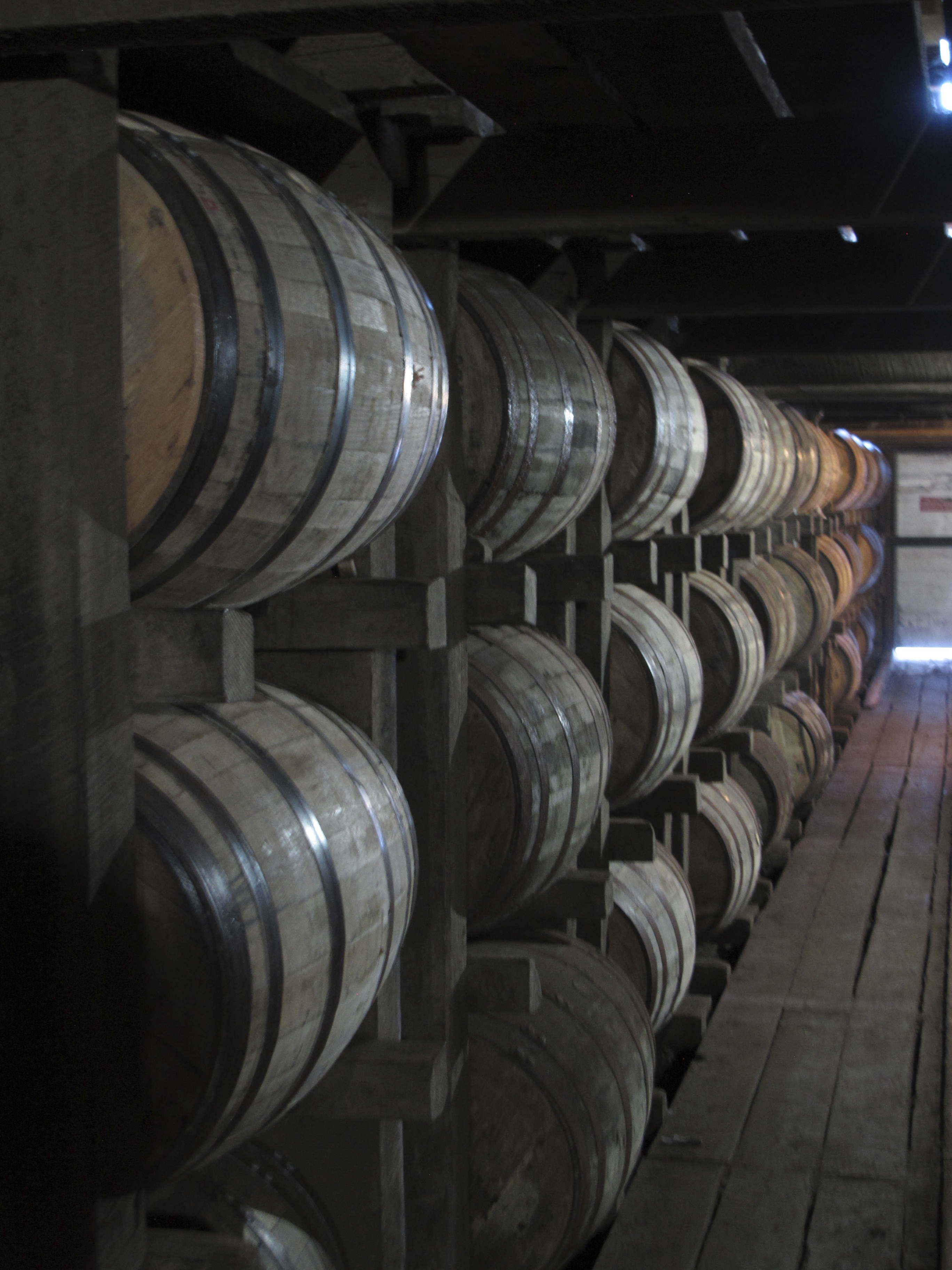 Bourbon supplies age in barrels at the Jim Beam distillery in Clermont, Kentucky. The process of making fine whiskey involves aging spirits to a golden brown, but a bourbon producing giant is going green along the way.