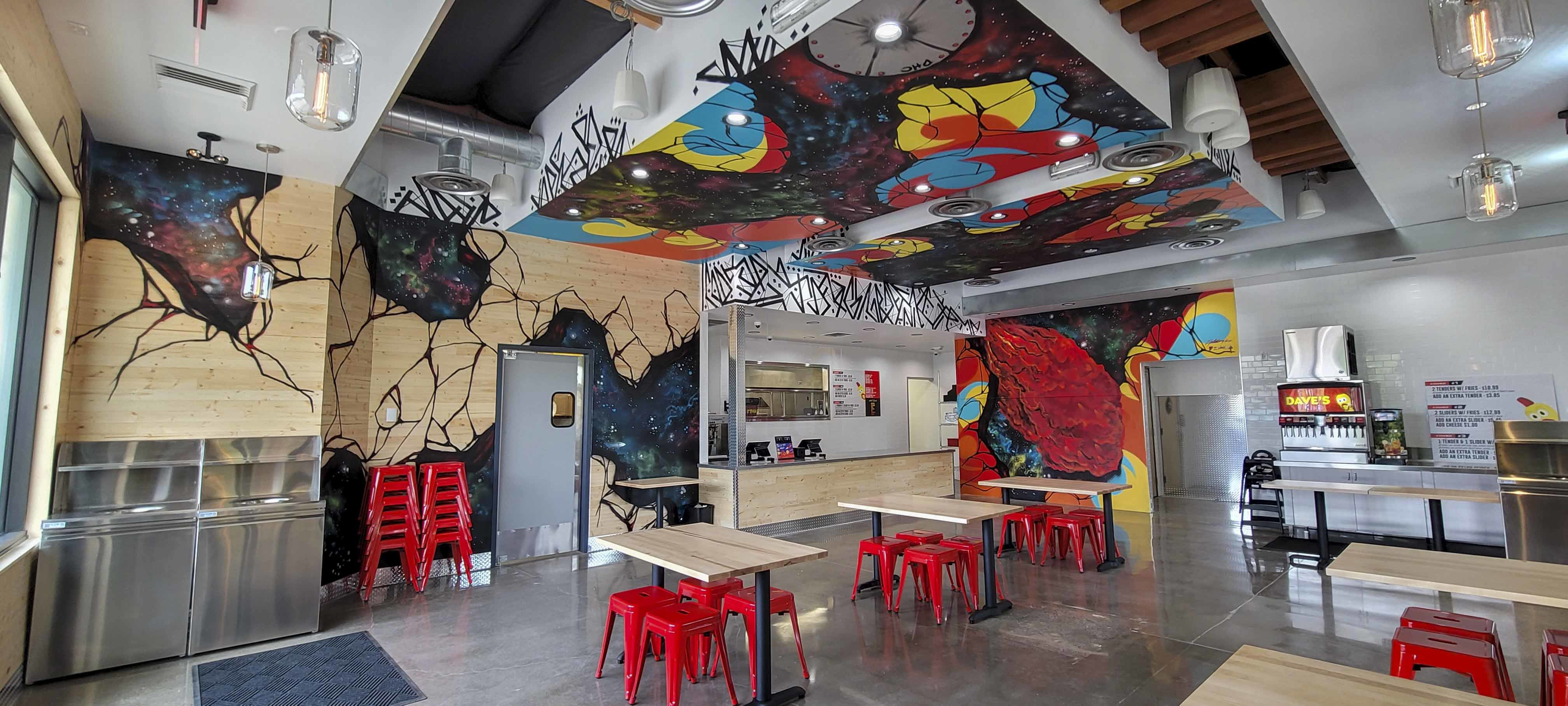 Walls of the Dave's Hot Chicken location in Tualatin include colorful murals, as if the wood is peeling away to reveal red, blue, and yellow bursts. The interior space also includes a number of tables and red stools, with a walk-up counter.