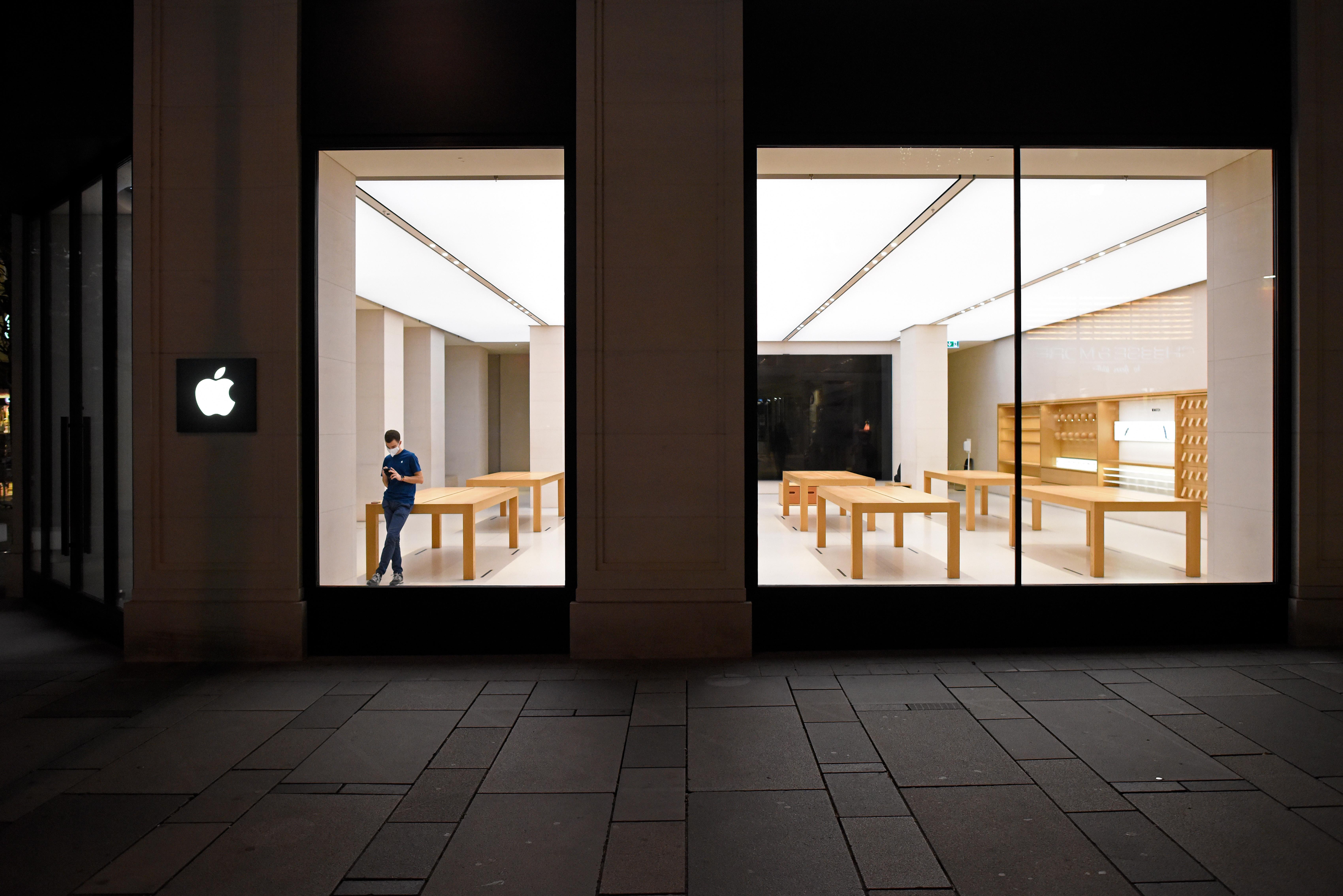A worker inside an empty Apple store.
