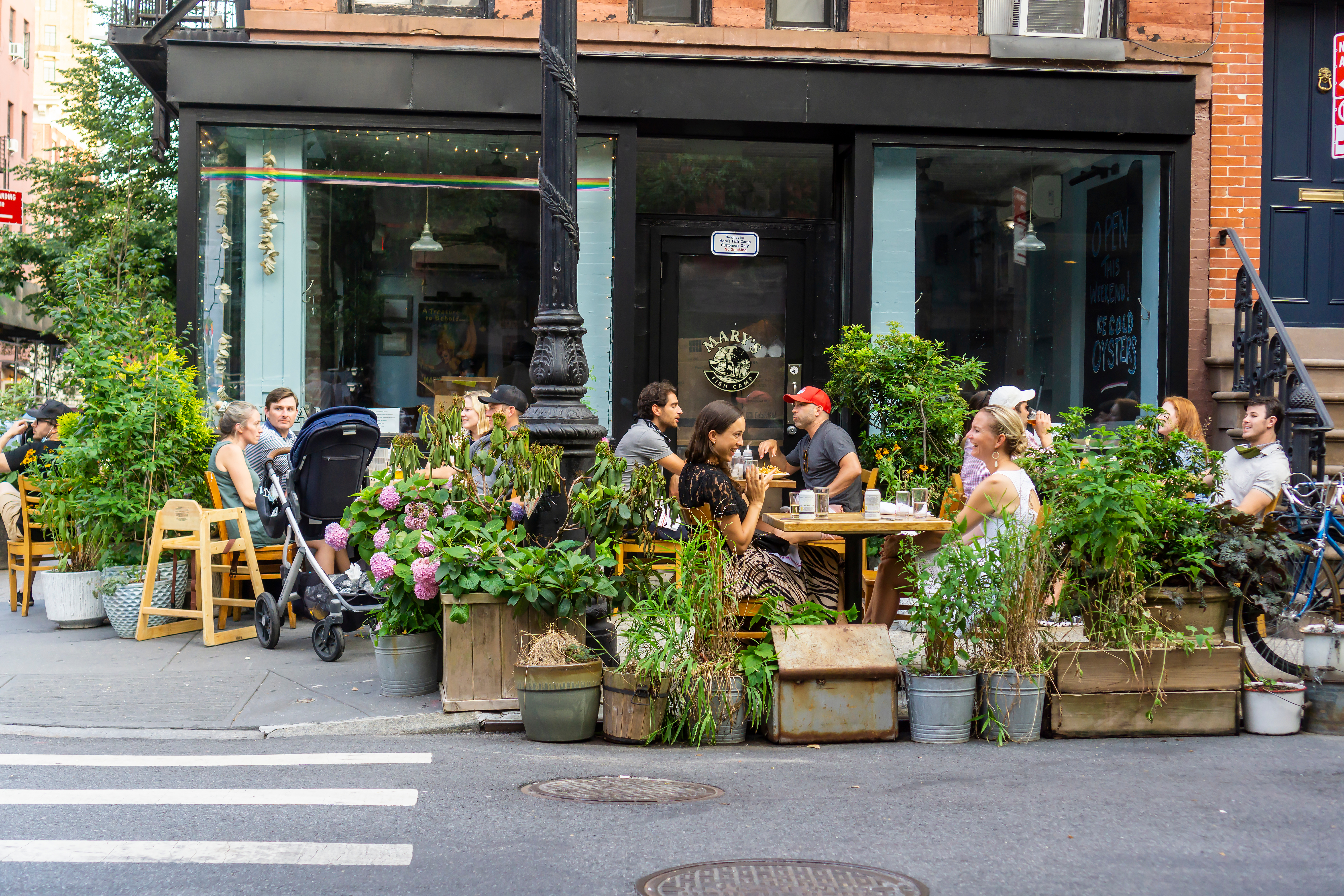 An outdoor dining set up on the street, featuring multiple tables of people surrounded by potted plants
