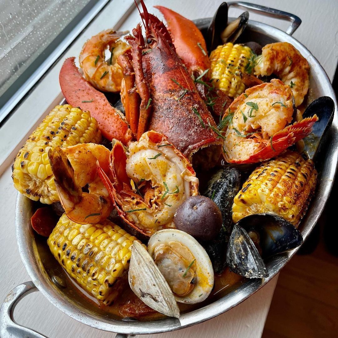 Overhead view of a seafood boil —corn on the cob, lobster, mussels, and clams —in an oval silver platter next to a window