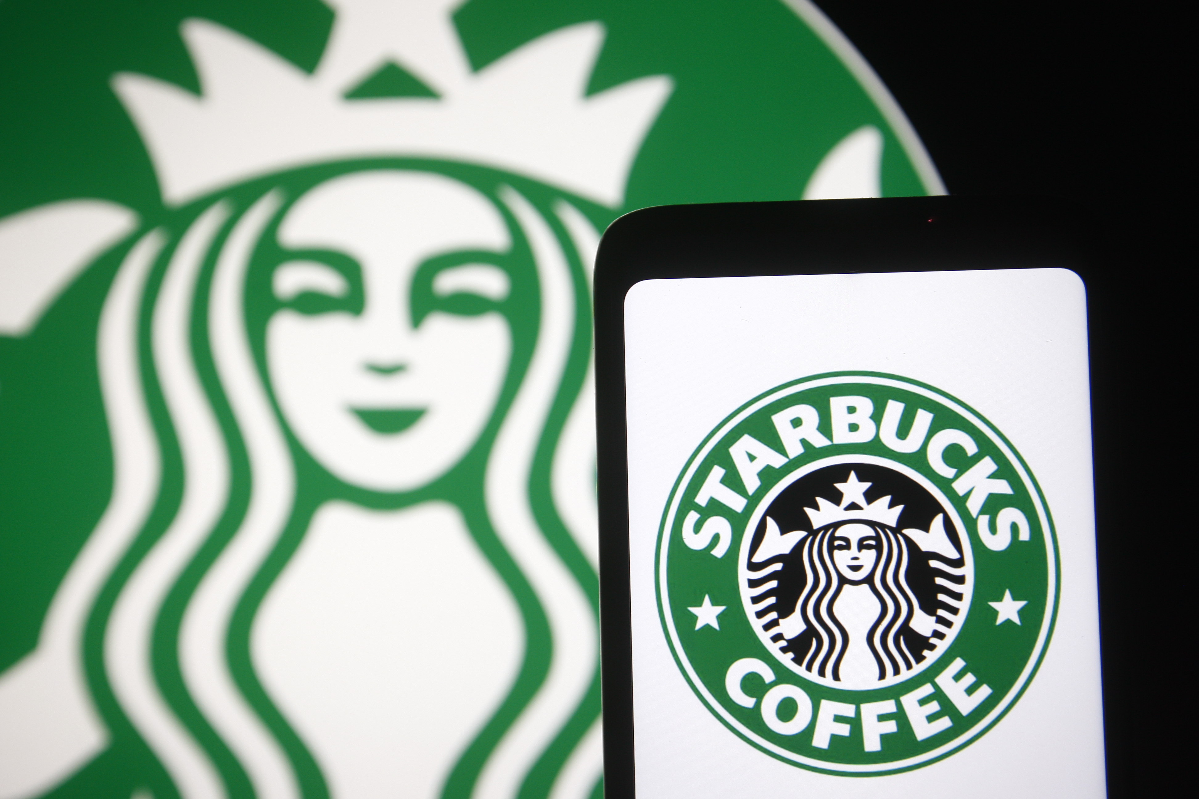 In this photo illustration, Starbucks logo is seen displayed...