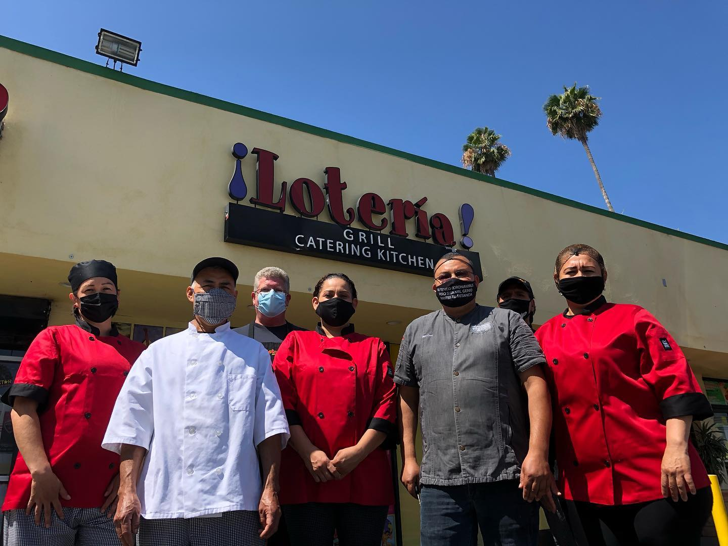 A group of workers in colorful kitchen outfits in front of a strip mall restaurant.