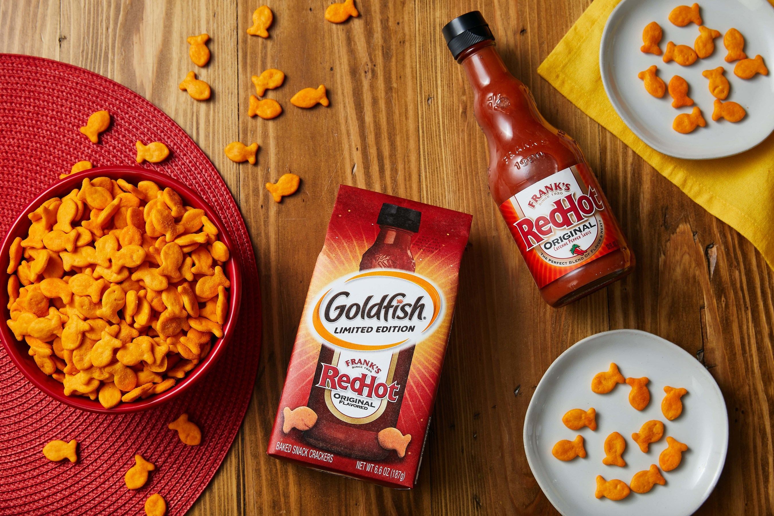 A top-down photo of Goldfish crackers in a bowl, a package of Goldfish, and a bottle of Frank's RedHot sauce.
