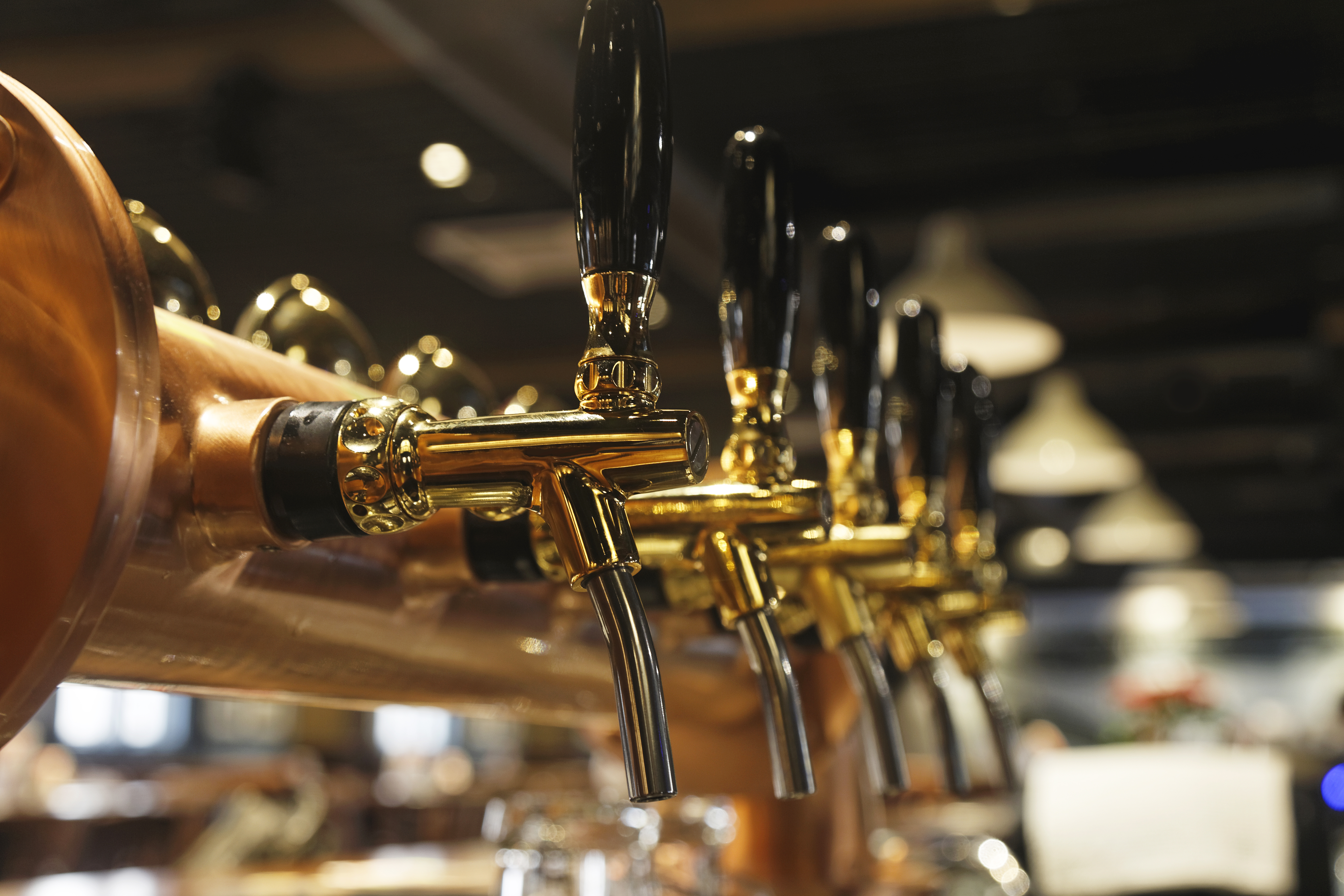 A row of brass taps inside a taproom at a brewery, shown closeup