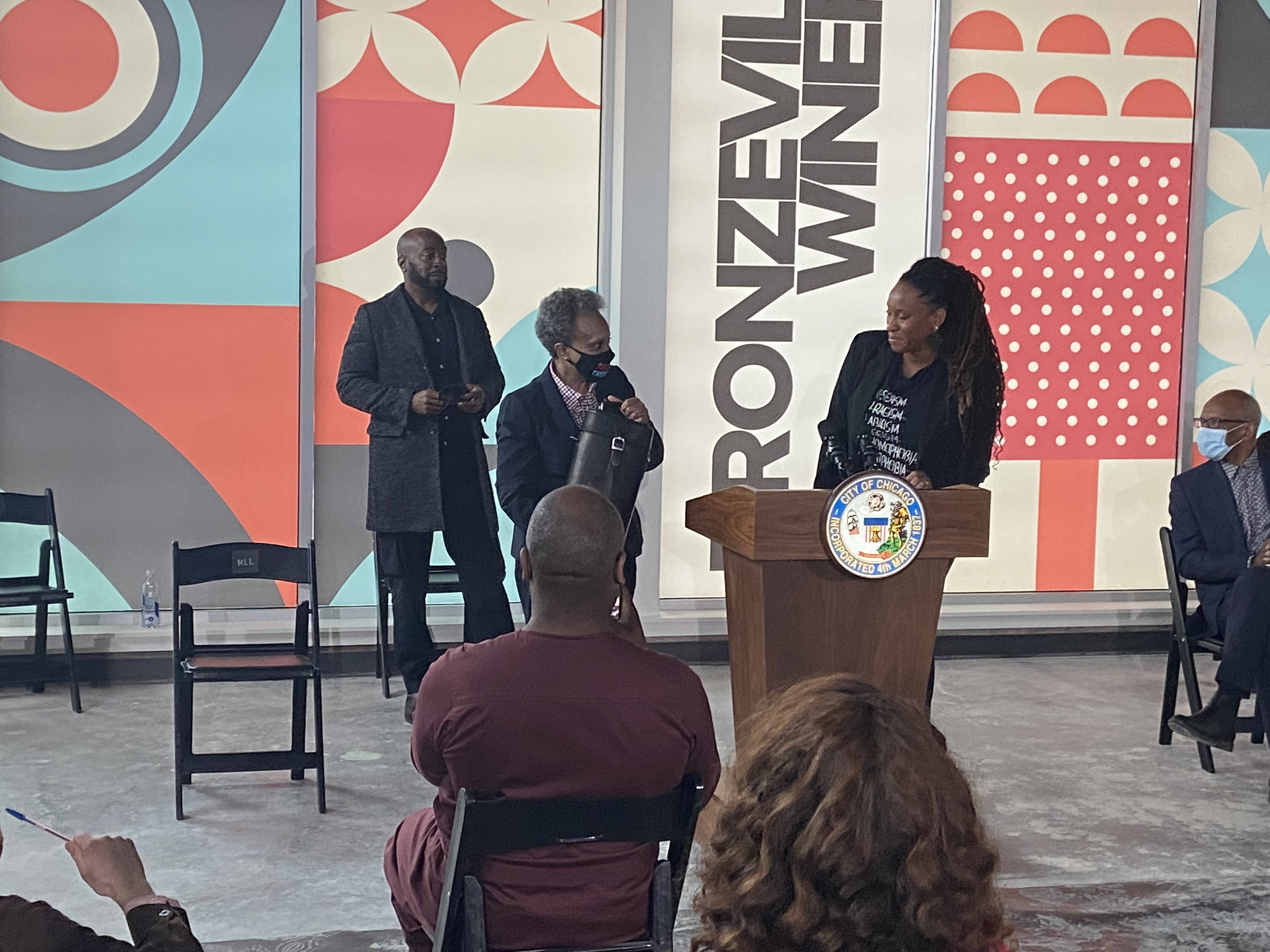 Mayor Lori Lightfoot receives a gift from Bronzeville Winery co-owners Cecilia Cuff (right) and Eric Williams (left)