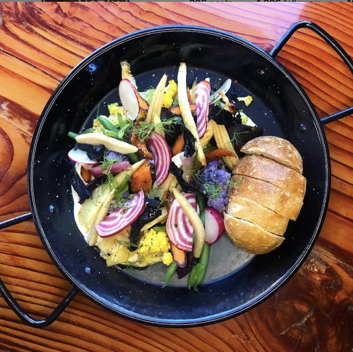 A black plate filled with candy-stripe beets, peas, carrots, and purple sprouting broccoli sits on a wooden table. The vegetables are held in place on a bed of white parsnip butter, with a few slices of bread next to the vegetables.