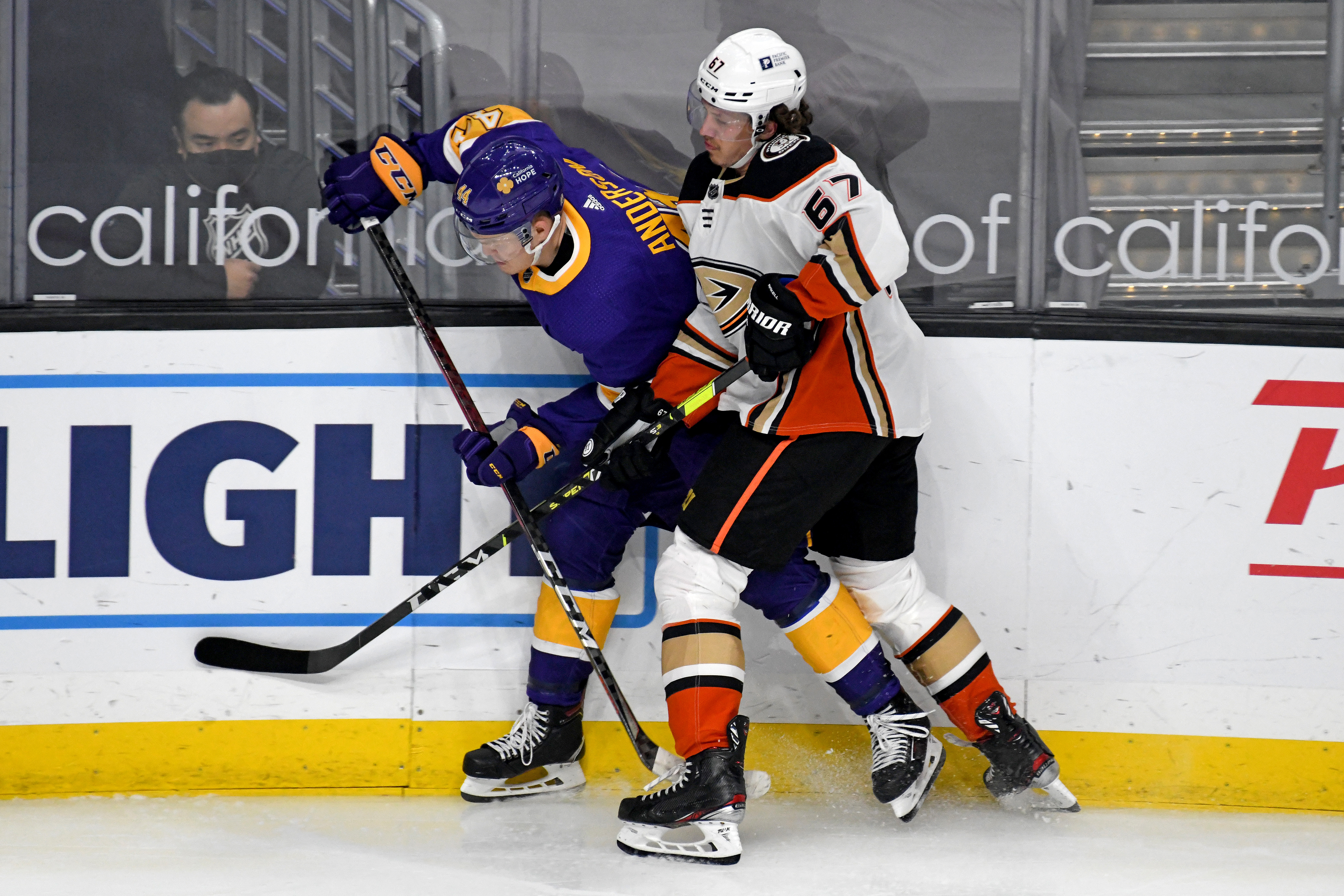 Los Angeles Kings Defenceman Mikey Anderson (44) and Anaheim Ducks Winger Rickard Rakell (67) battle along the boards during an NHL game between the Anaheim Ducks and the Los Angeles Kings on April 26, 2021, at the Staples Center in Los Angeles, CA.