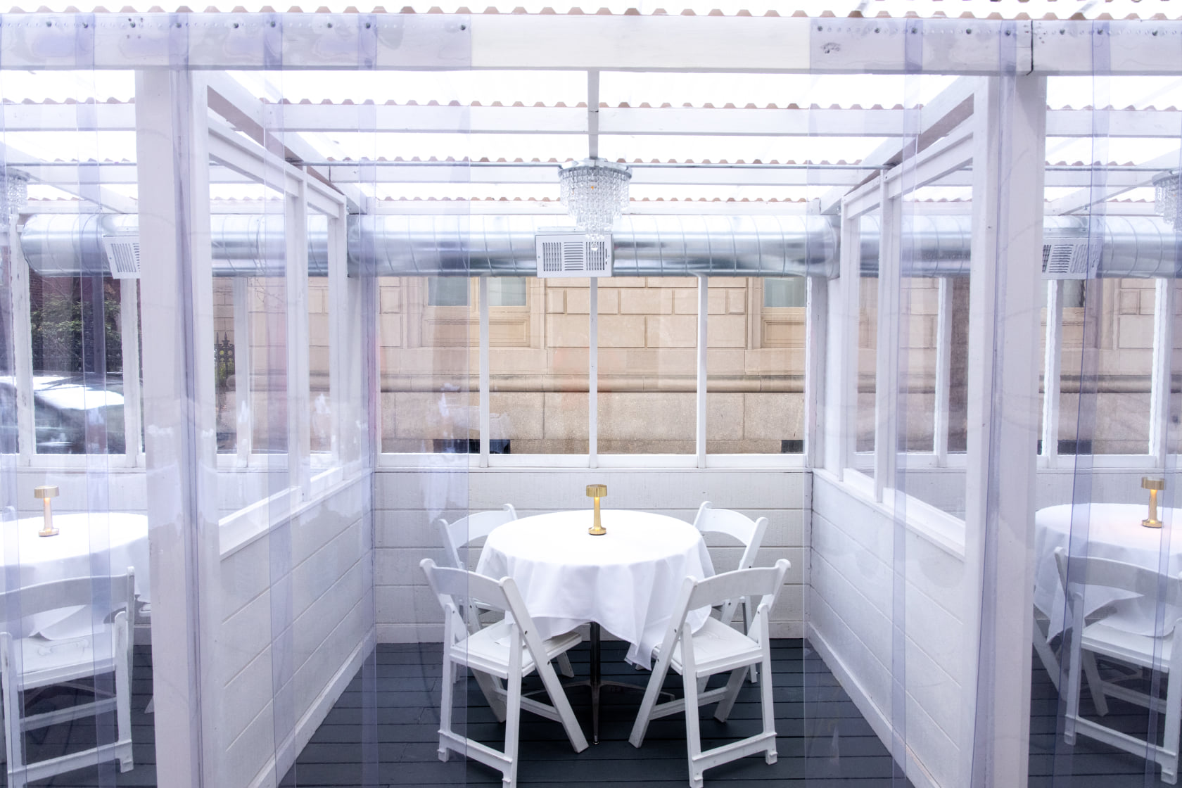 An enclosed outdoor seating area with a bright white interior, a round white table and table cloth with bright white patio chairs.