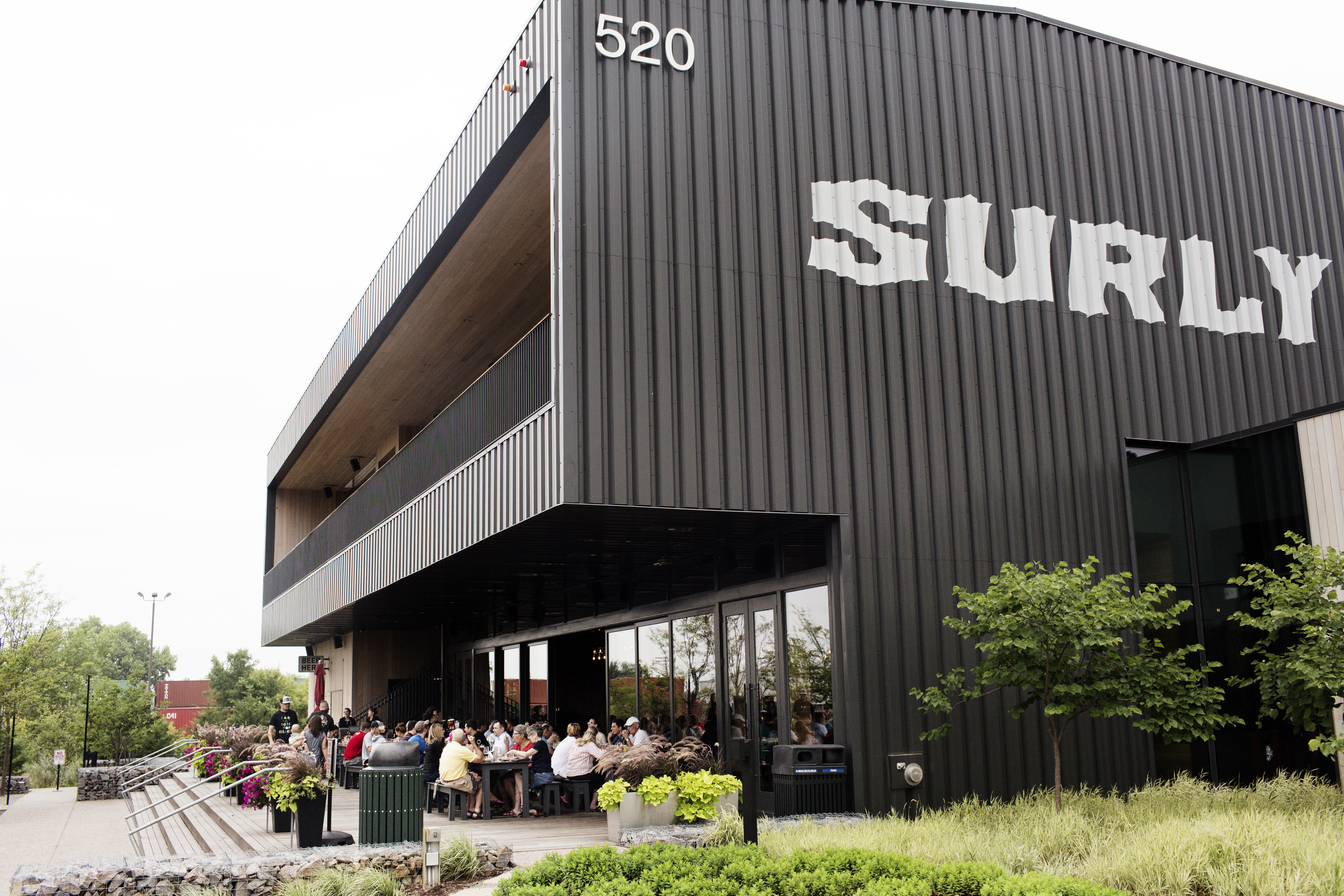 The black Surly building rises like a monolith over a small sidewalk patio with a table full of people