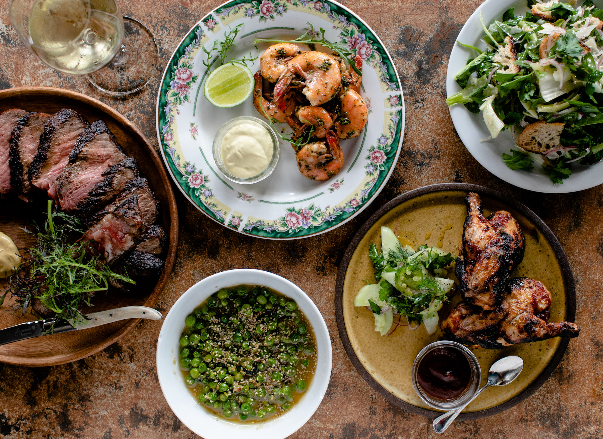 An overhead shot of rustic country plates filled with Southern cooking and grilled items.