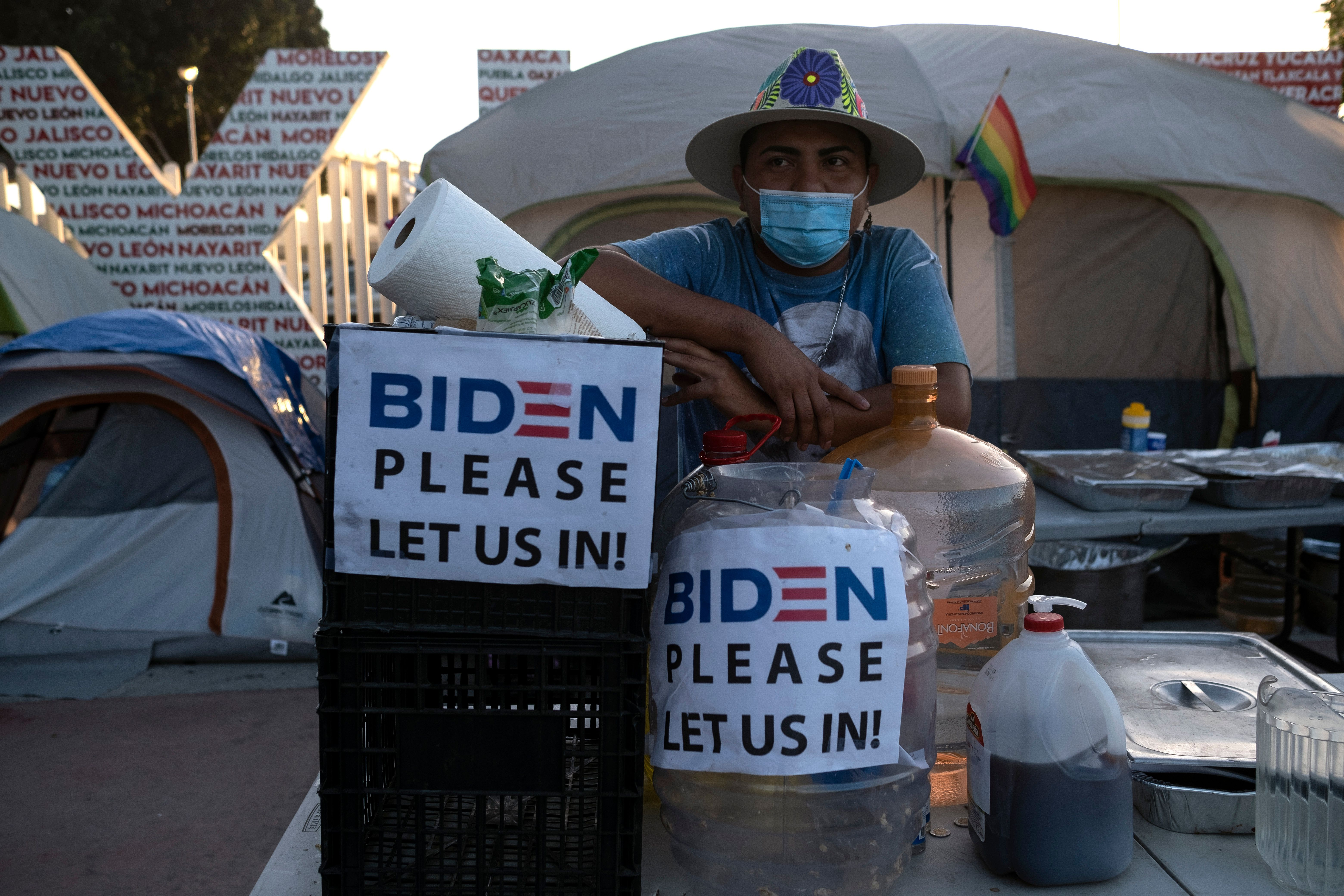 """A migrant stands in an outdoor kitchen beside a tent with signs that read """"Biden please let us in!"""""""