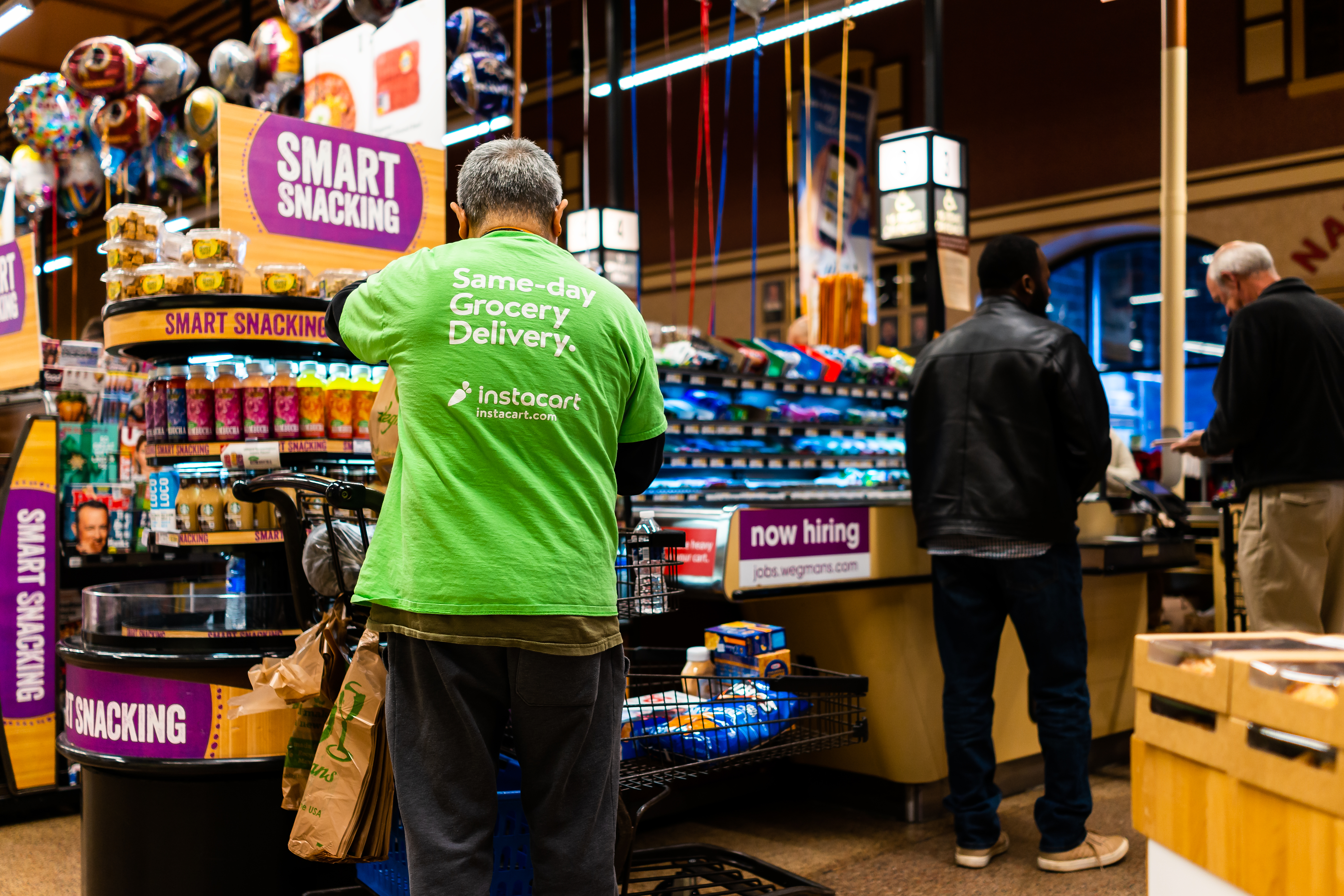 A man in a grocery store, with his back turned to the camera, wearing a neon green Instacart t-shirt