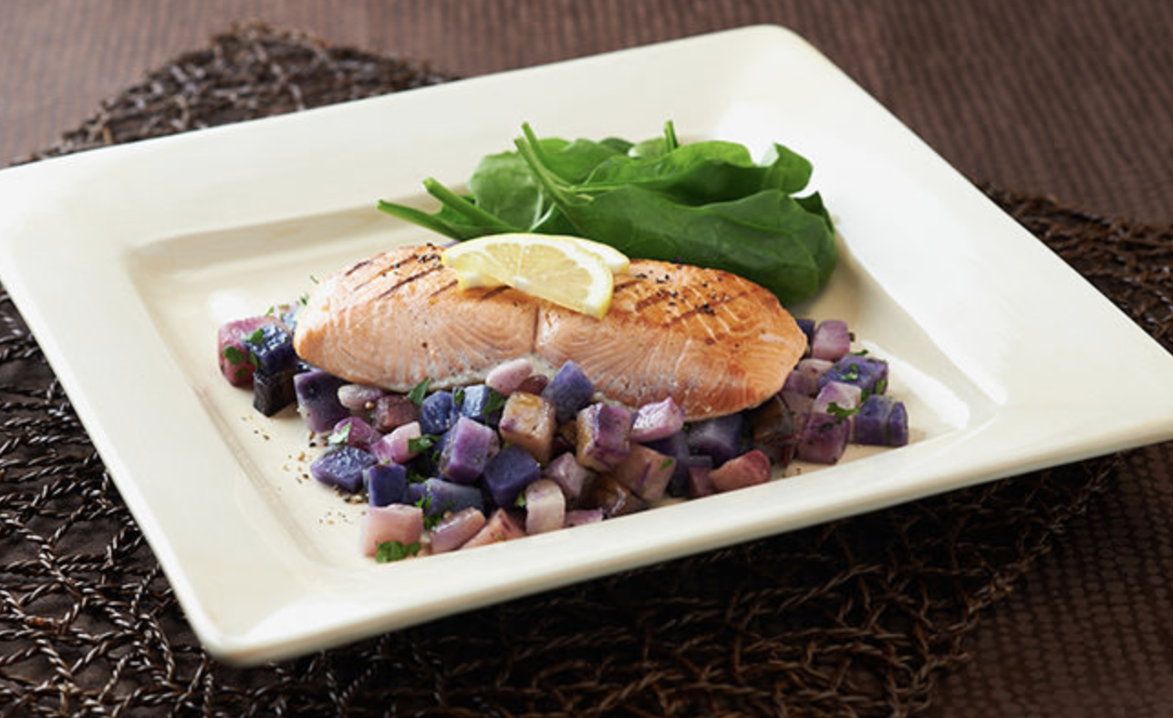 A cooked salmon on a plate with a lemon slice on top and roasted purple-colored potatoes on the side