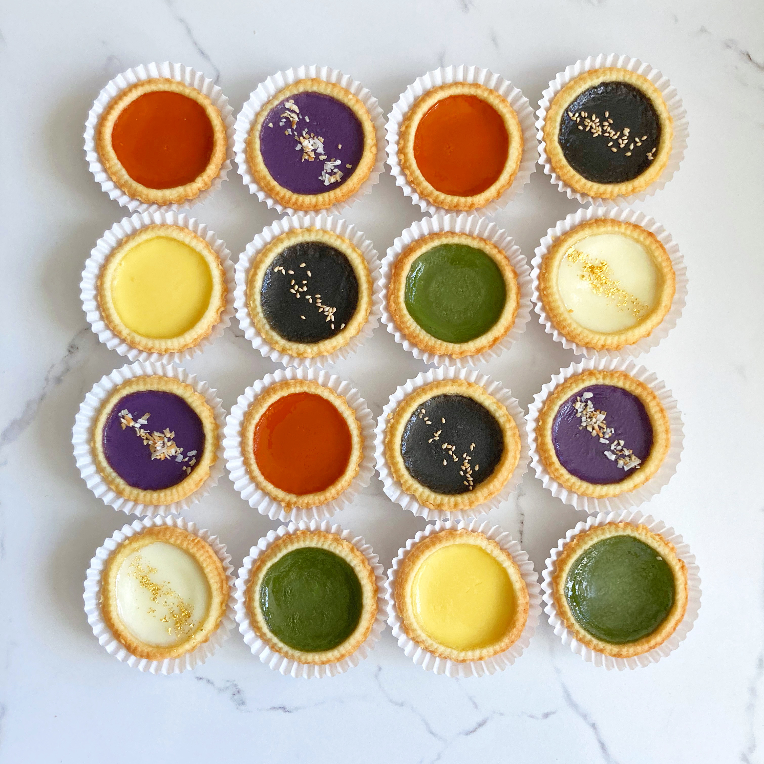 Dan tat or Hong Kong-style egg tarts in various flavors like almond jello, matcha, and ube from Spoons Patisserie in Los Angeles and San Francisco.