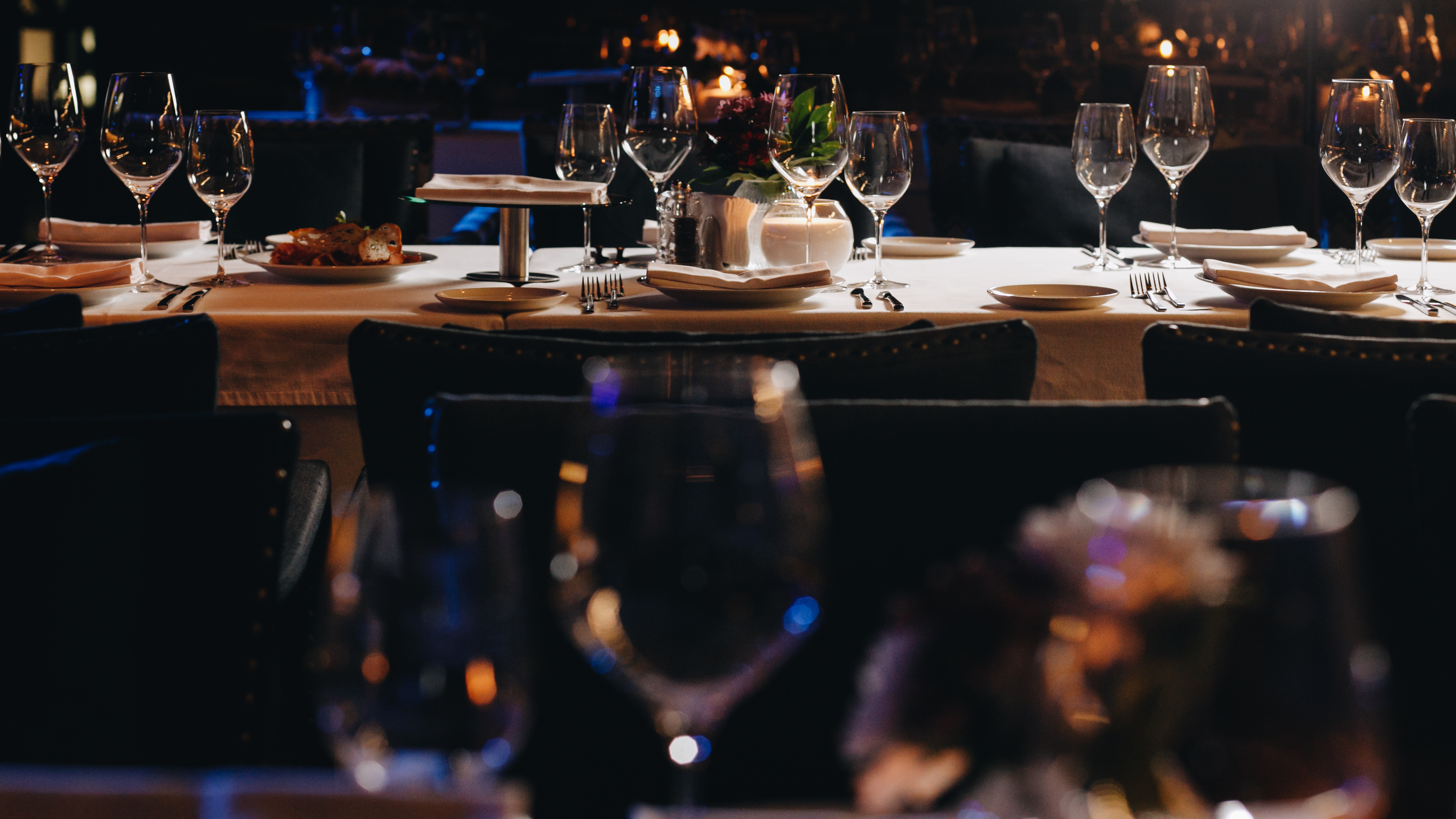 Empty tables with settings and wine glasses in a dining room that's moodily lit
