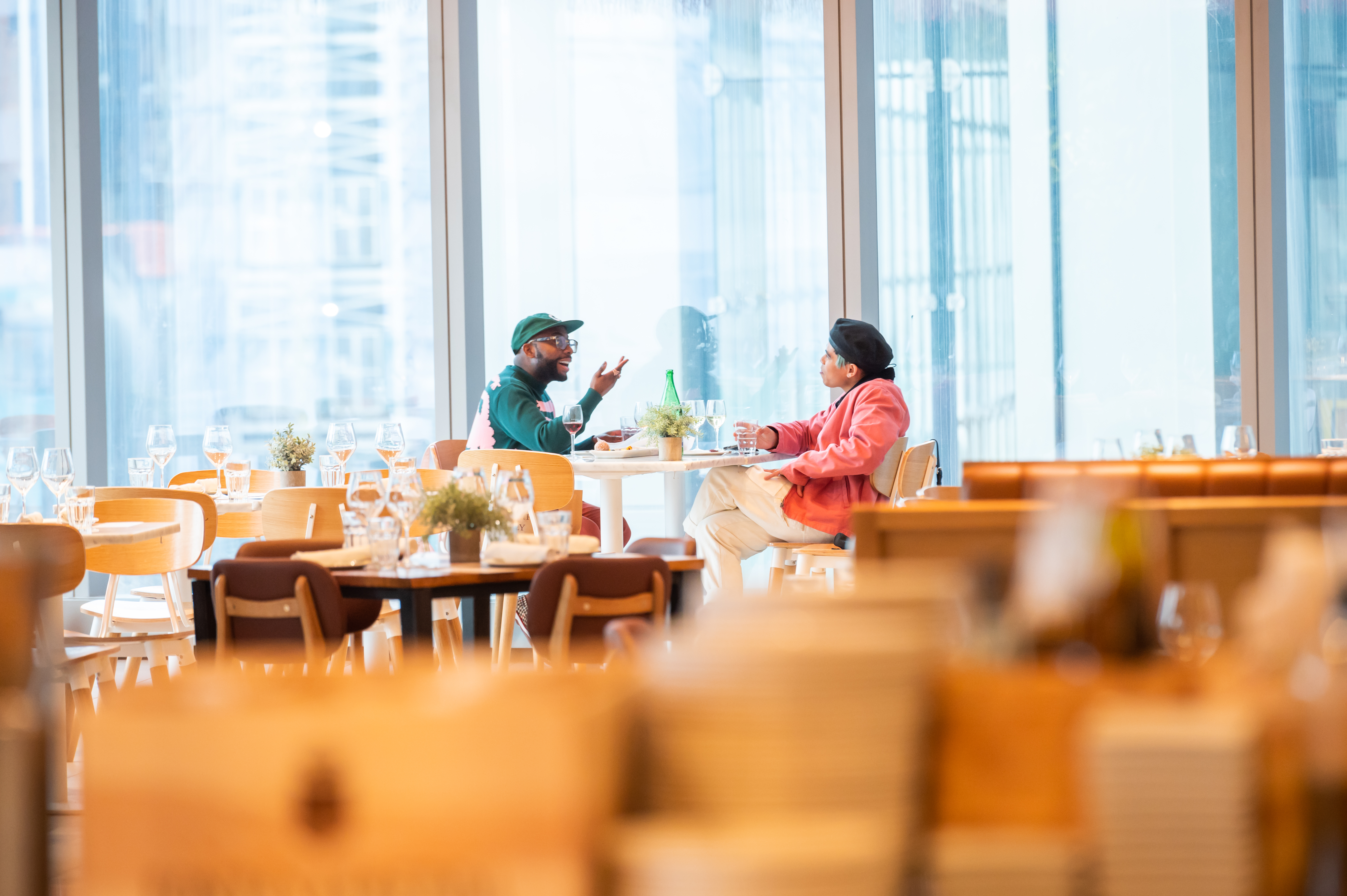 Two people eat in a dining room full of empty chairs and tables.