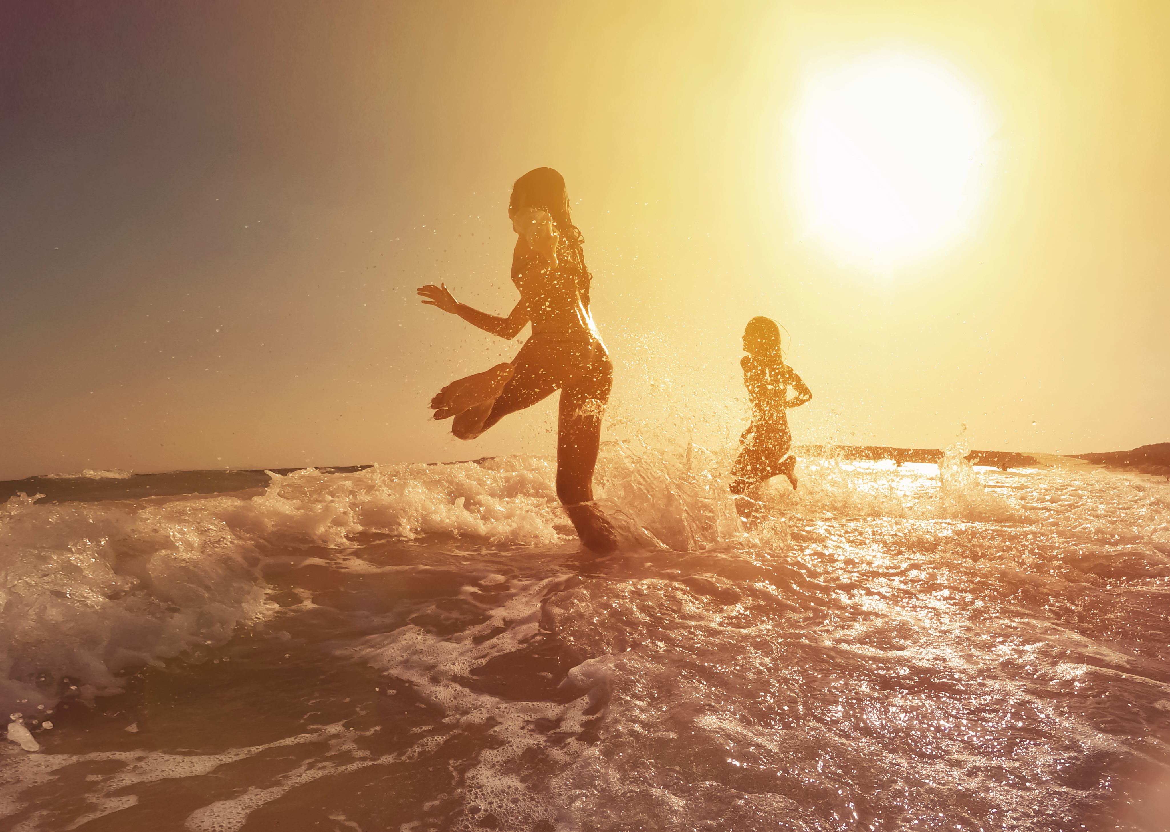 Two people running into the ocean on a sunny day.