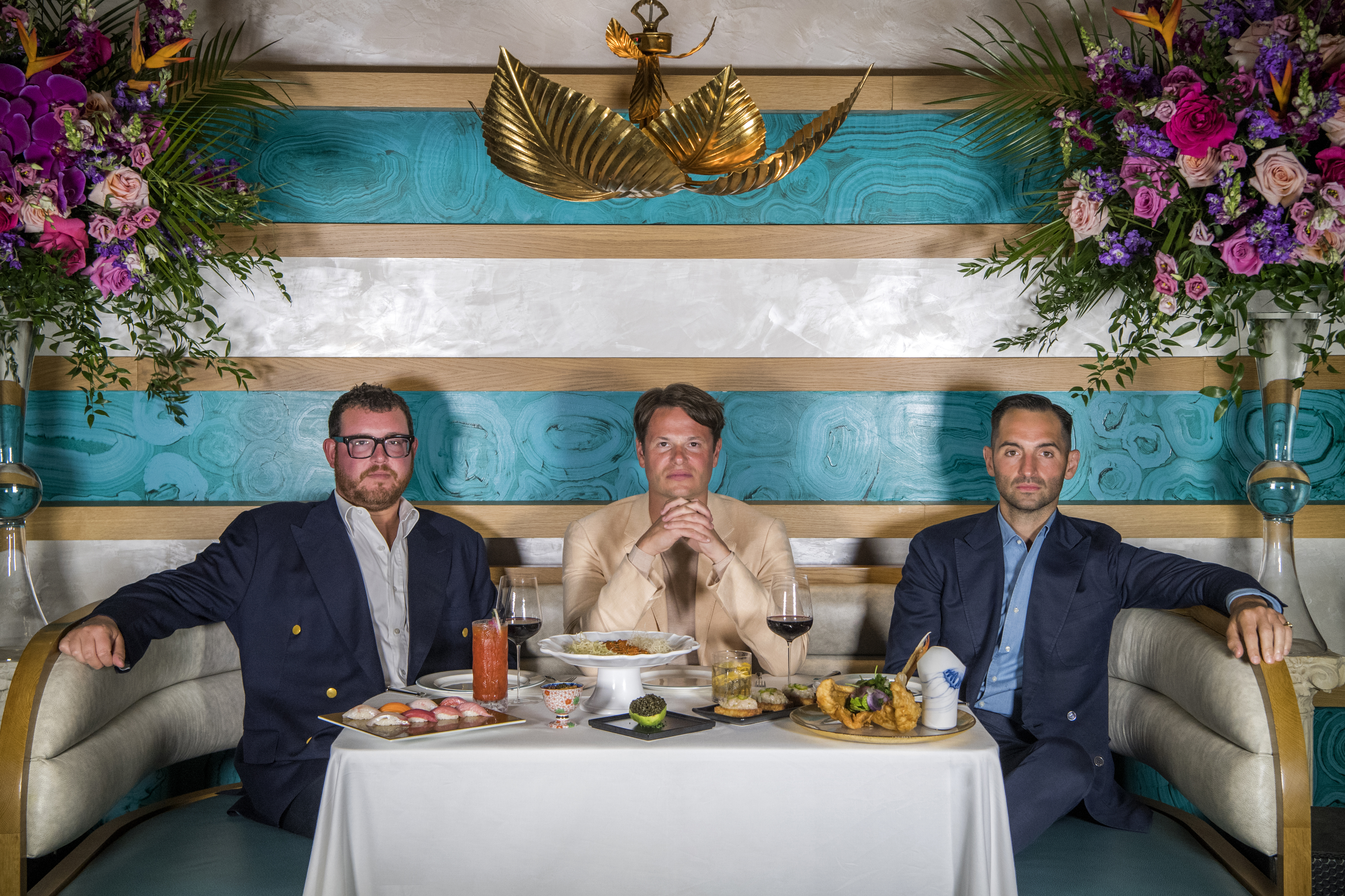 Three men with serious expressions sit at a restaurant booth behind a table laden with food. Above them is a chandelier in the shape of large gold leaves, and in either corner of the frame is a large bouquet of flowers