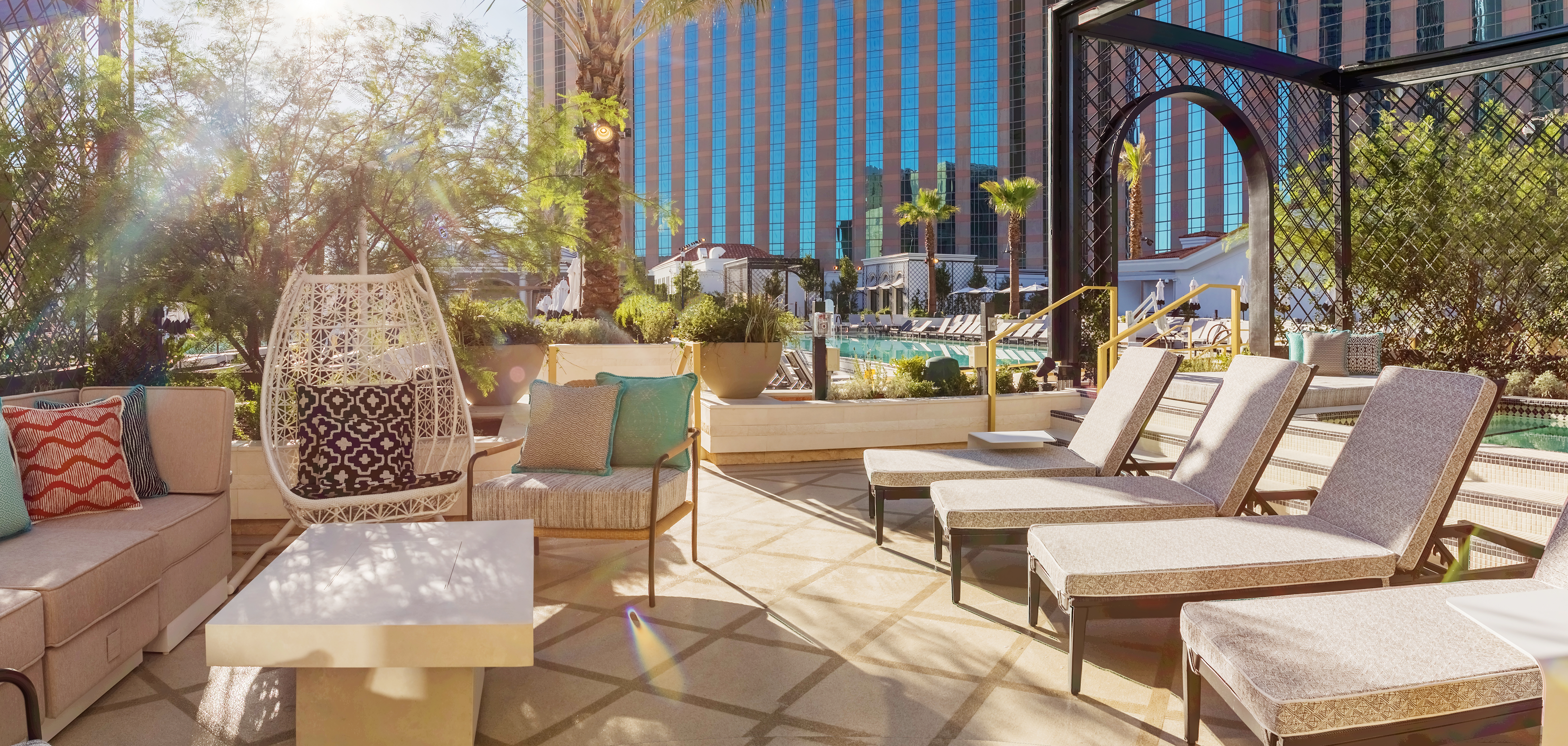 Chaise lounges sit in front of a pool with a hotel in the background