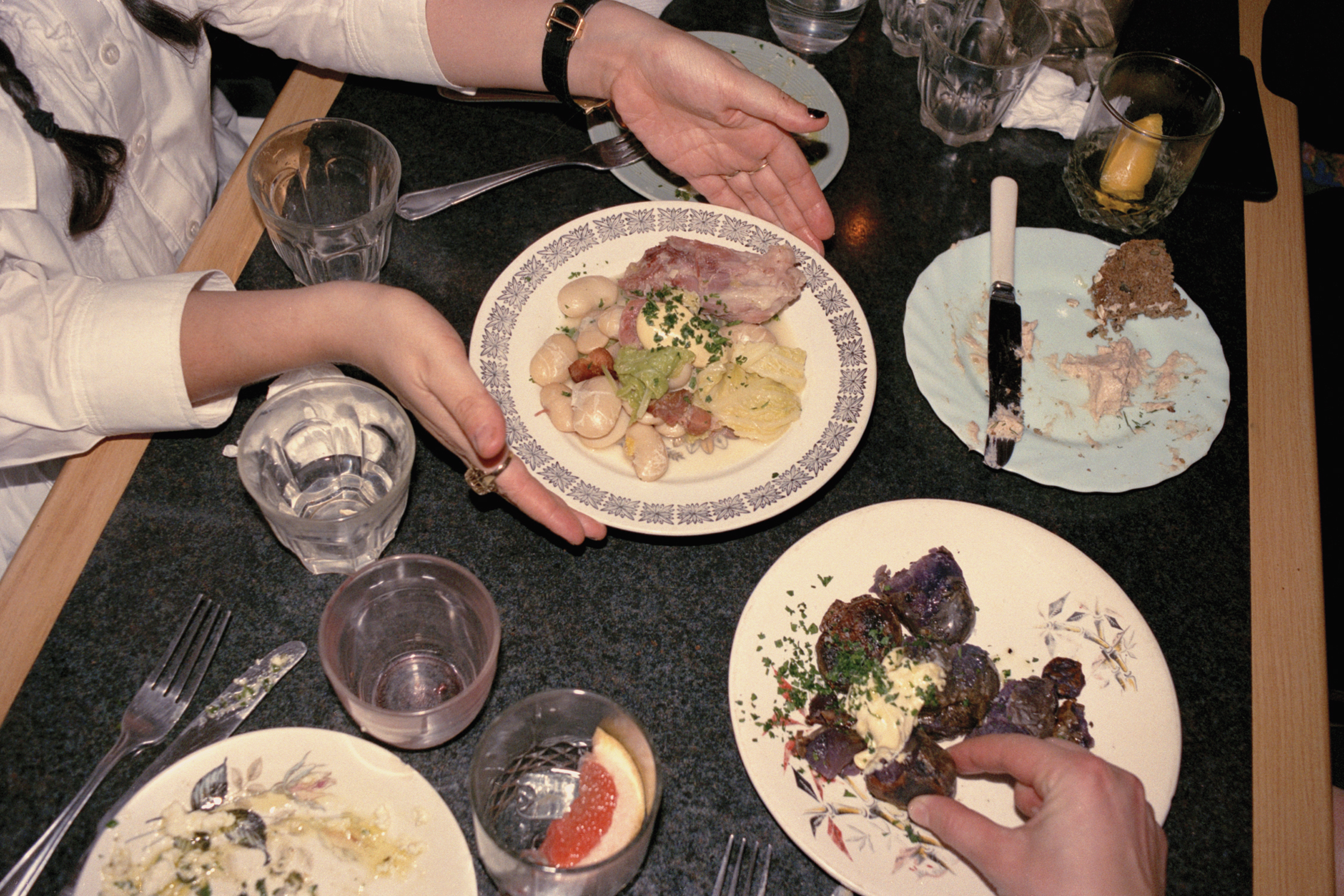 Overhead table shot of someone passing a plate of ham, butter beans, and cabbage at one of ex-River Cafe chef Max Rocha's first supper clubs, Pacific Social Club in 2016.