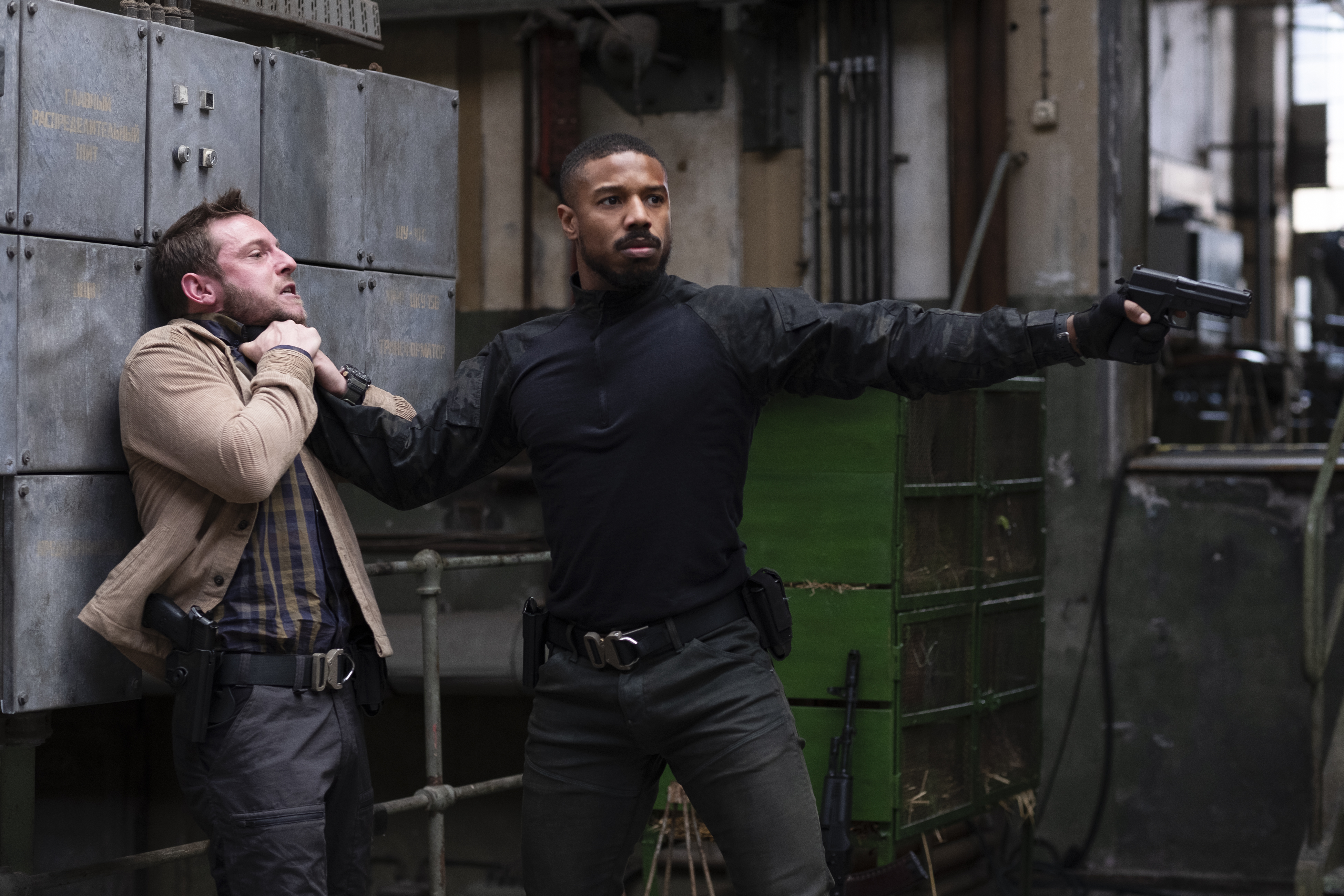 Michael B. Jordan as Navy SEAL John Clark pins a man to a wall by the throat with one hand and points a handgun with the other in Without Remorse