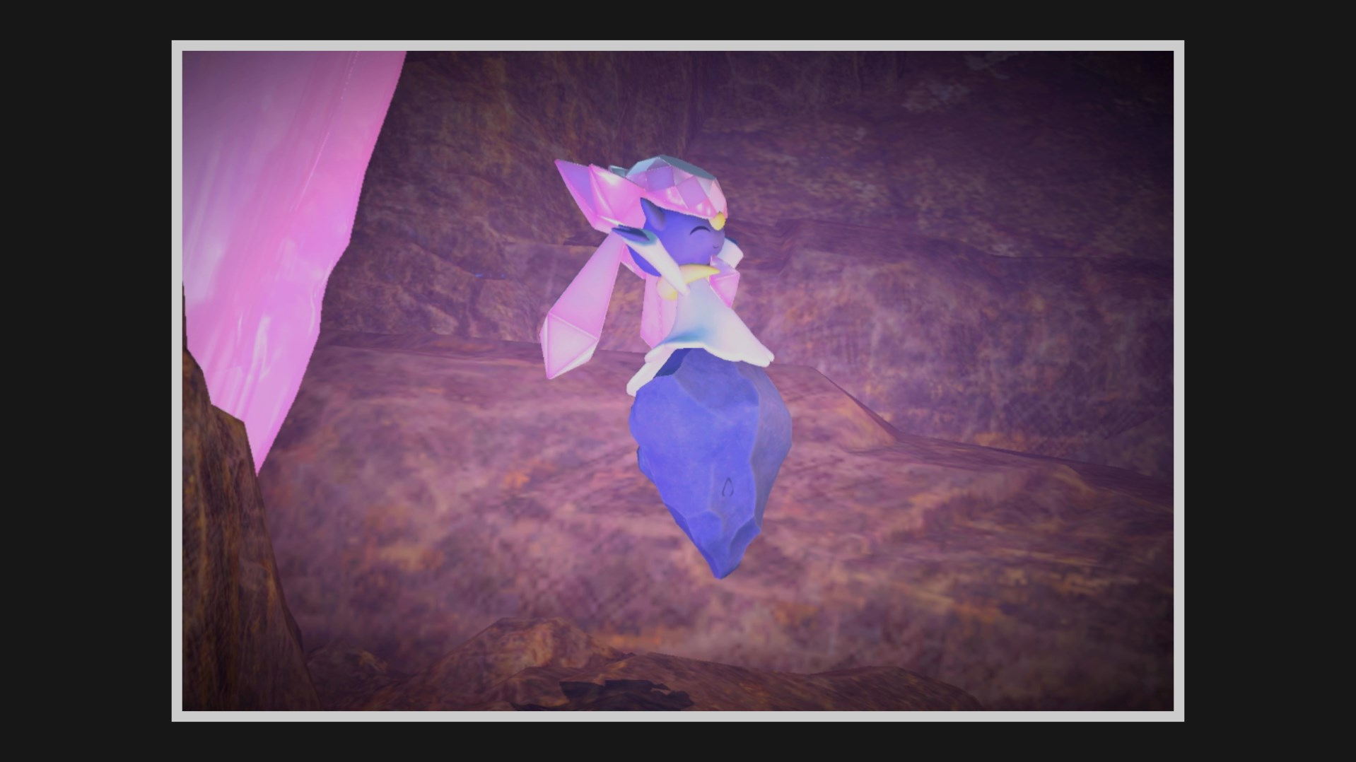 Diancie cheers happily, glowing pink in a cave