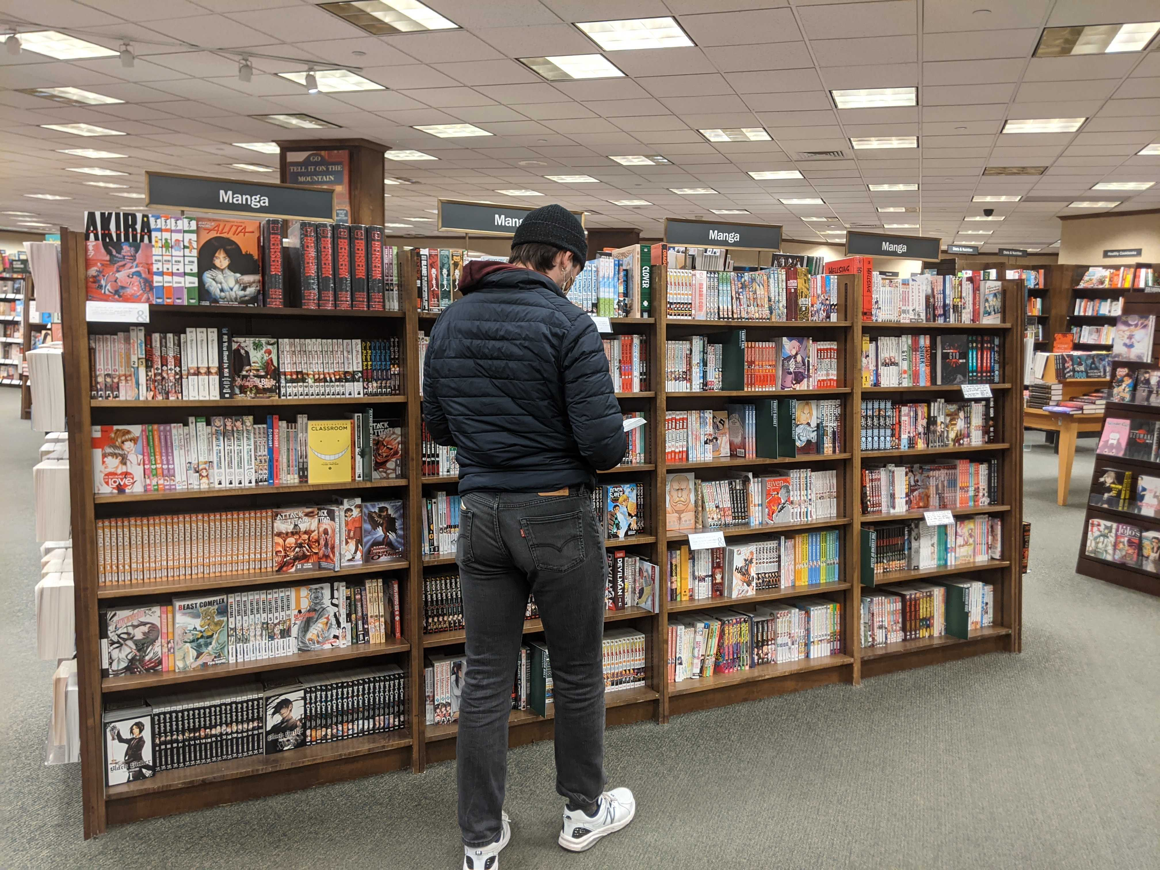 A young man standing browsing some manga in the manga section of Barnes and Noble