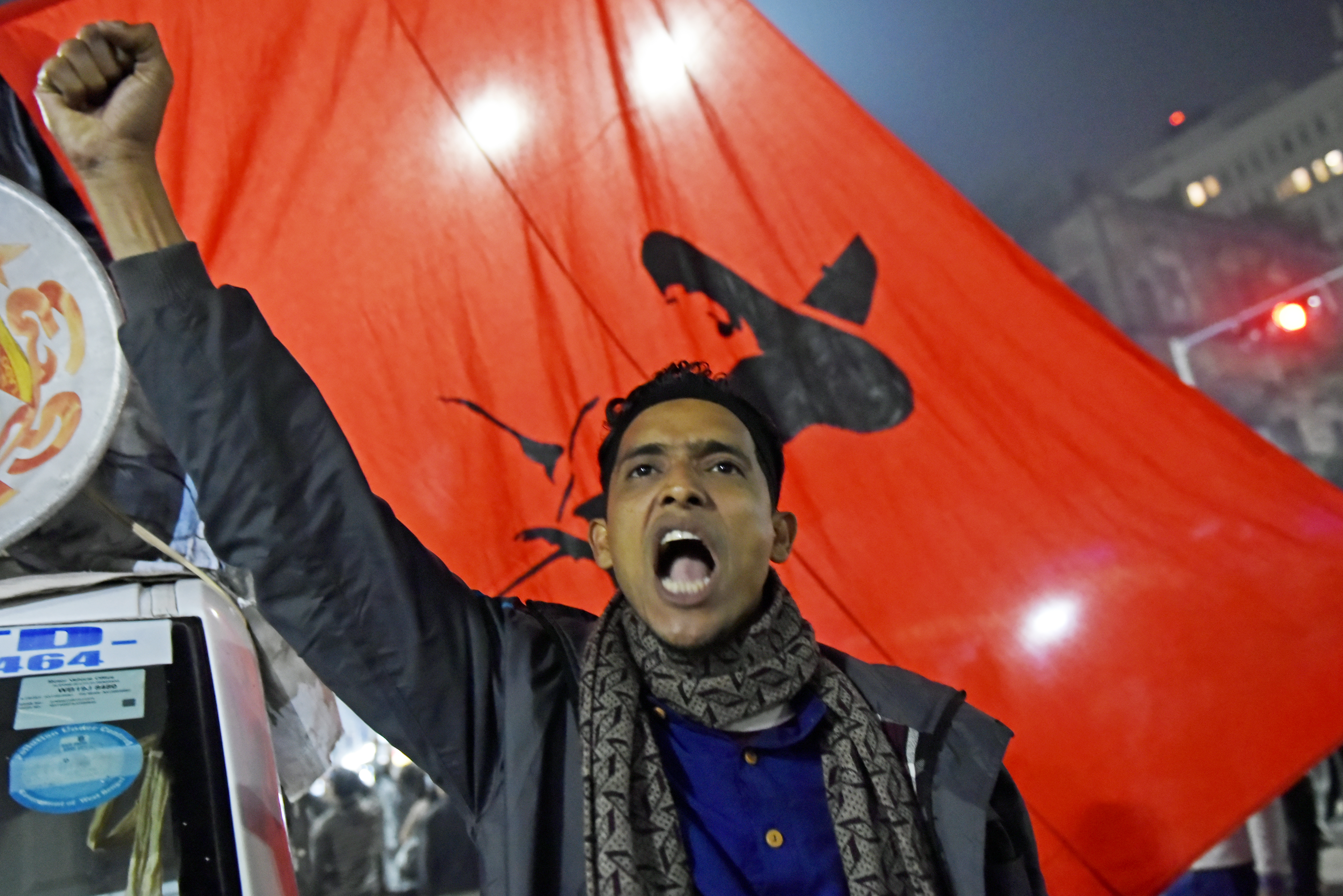A protester shouts and raises a fist in front of a red flag.