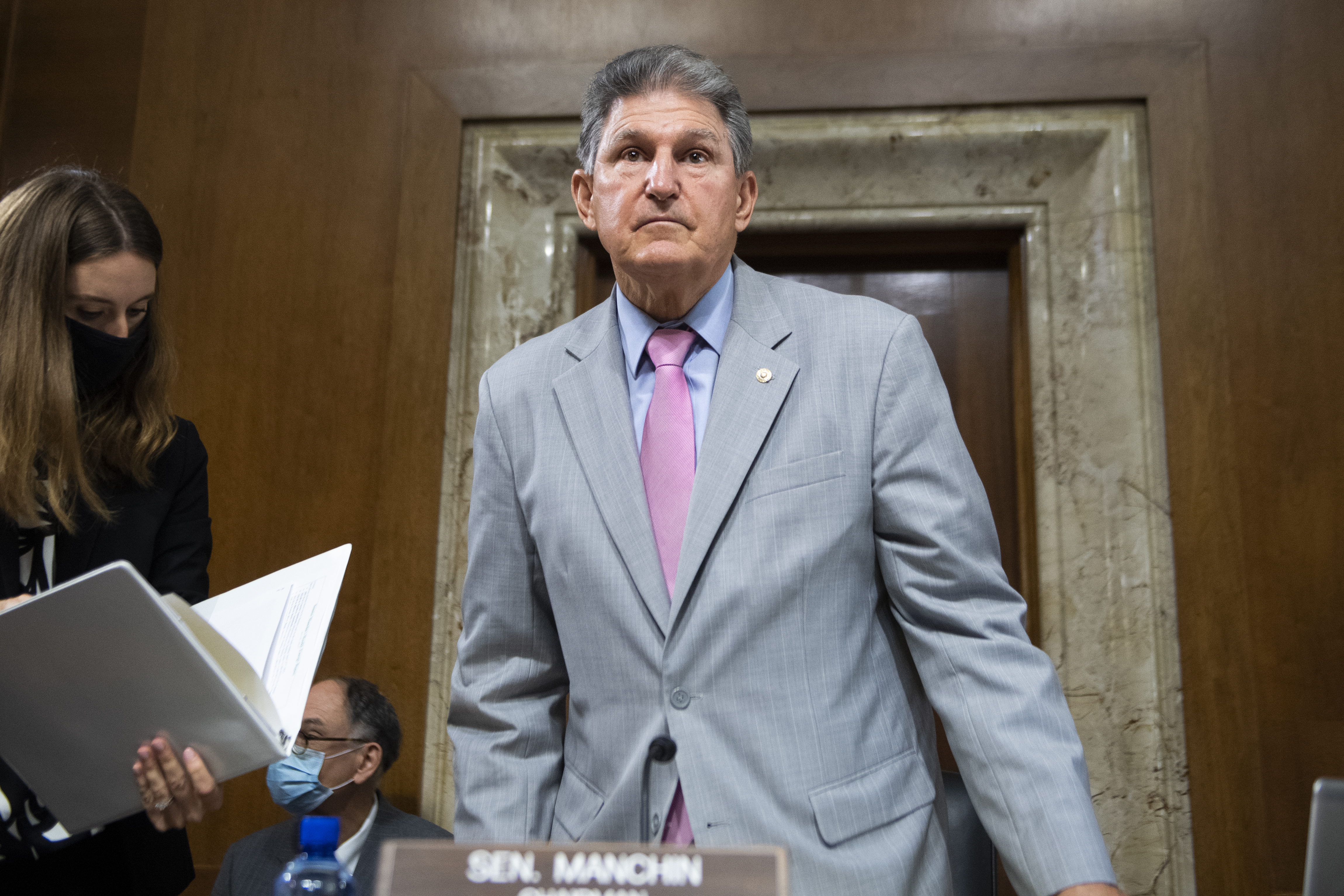 Manchin enters a Senate hearing room, dressed in a light gray suit, blue shirt and pink tie.
