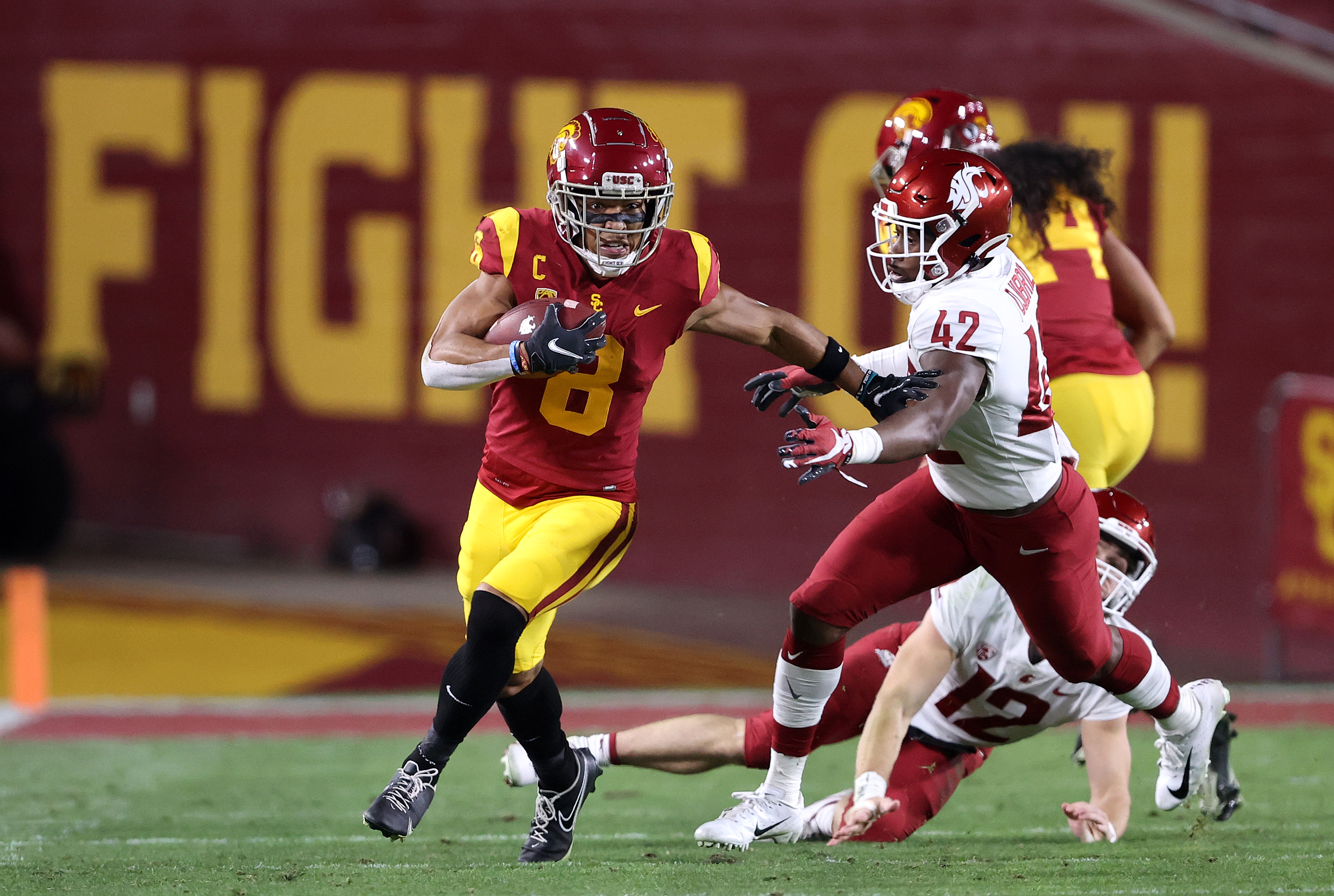 Amon-Ra St. Brown #8 of the USC Trojans eludes the tackle of Halid Djibril #42 of the Washington State Cougars on a punt return during the first half of a game at Los Angeles Coliseum on December 06, 2020 in Los Angeles, California.