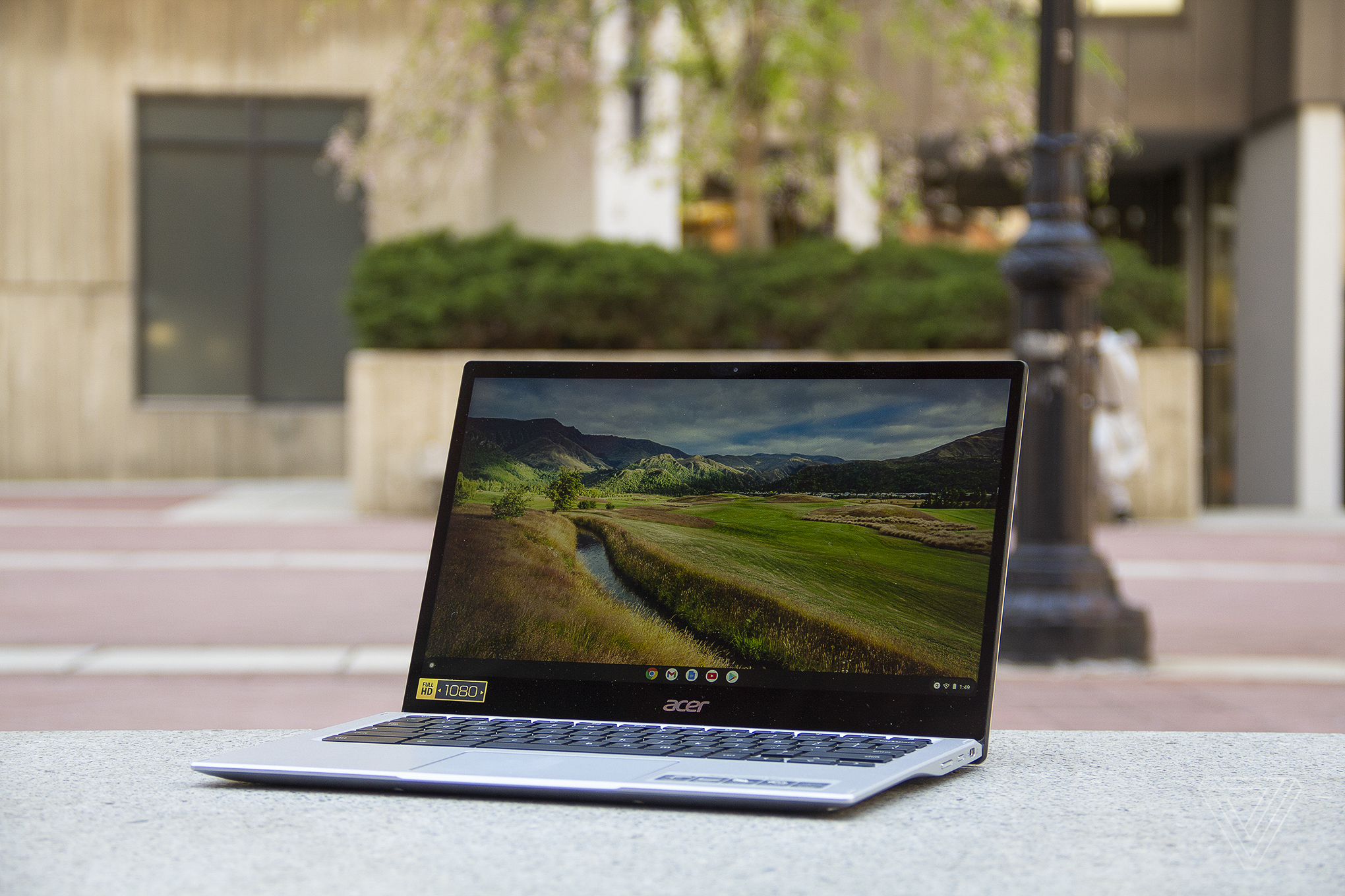 The Acer Chromebook Spin 513 sits on a stone bench, open, angled to the left. The screen displays a pastoral scene.