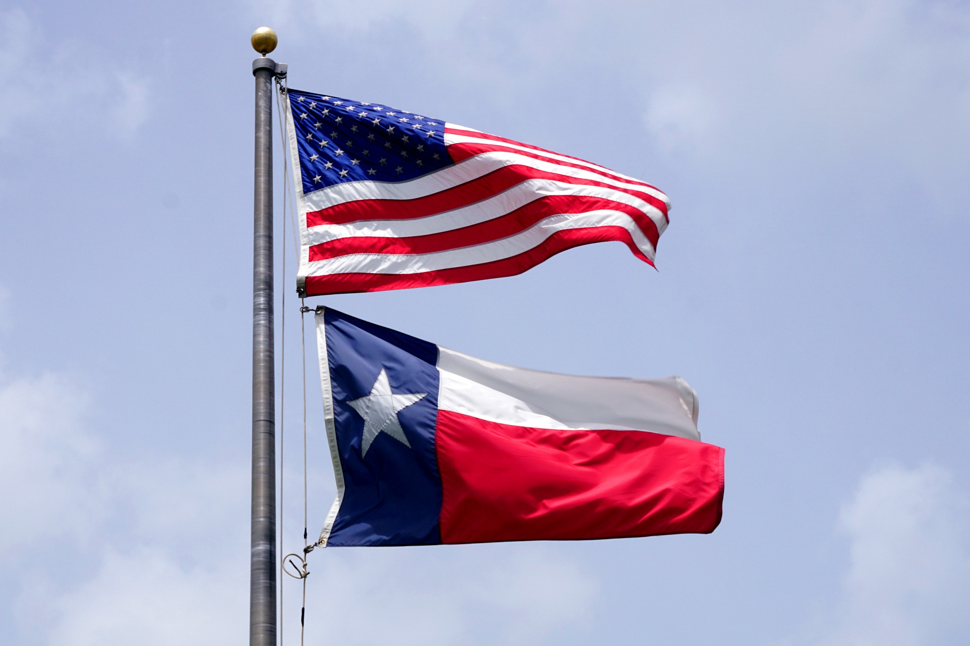 The state flag of Texas is shown flying on a flag pole beneath the flag of the United States.