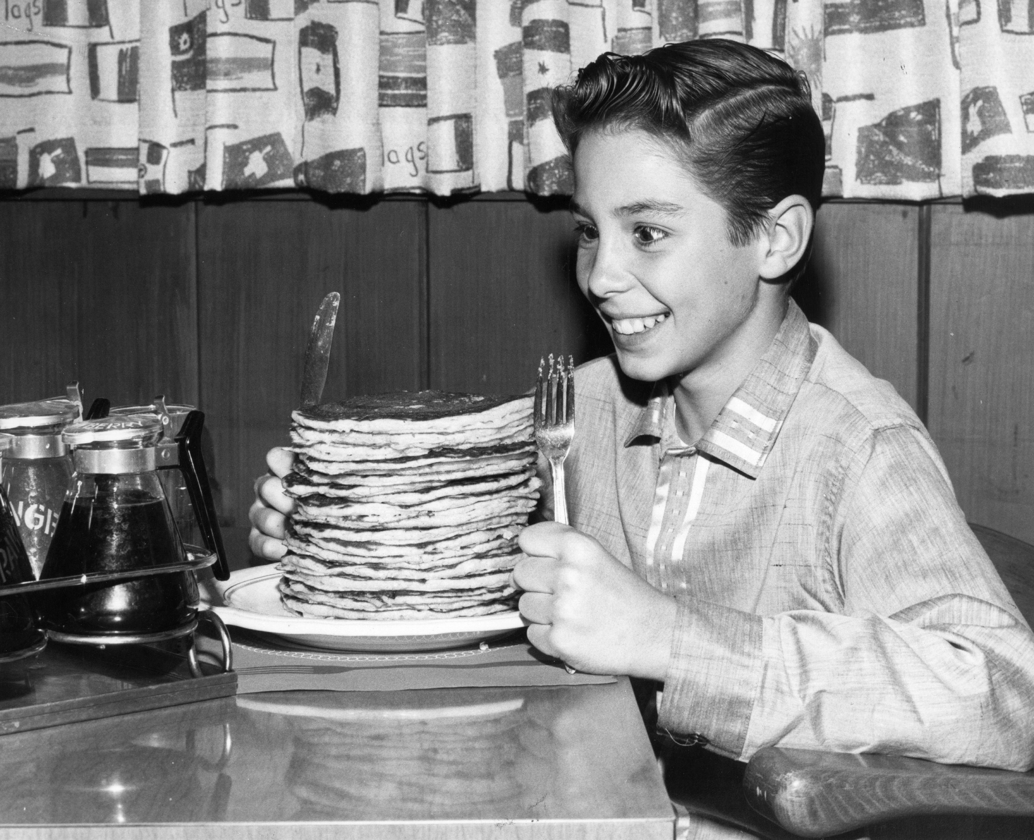In this file photo, circa 1960, child actor Johnny Crawford looks forward to eating a pile of pancakes in an International House of Pancakes, a chain of eateries in the US started in 1958 by Californian brothers Al and Jerome Lapin.