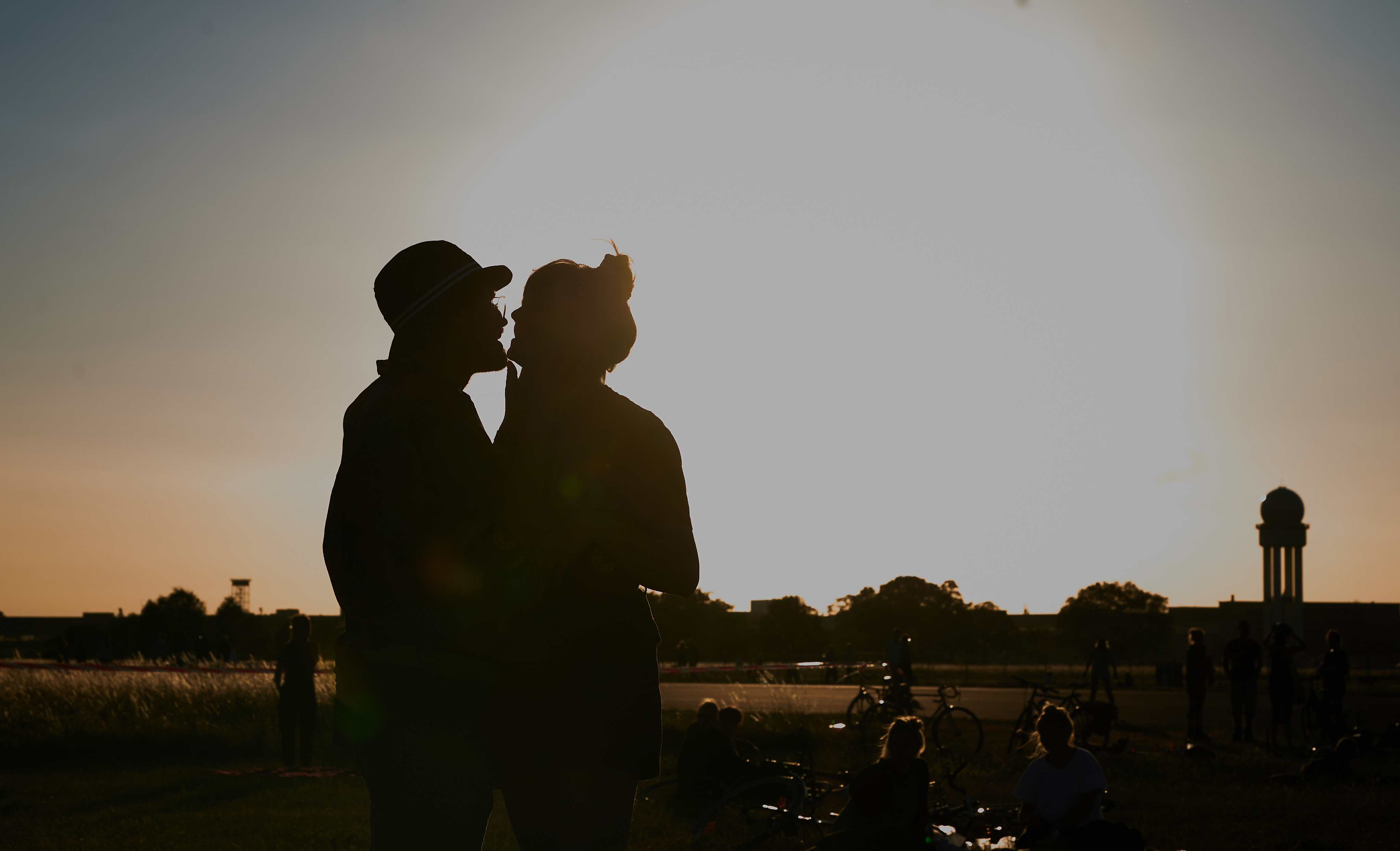 A kissing couple silhouetted against a twilit sky.