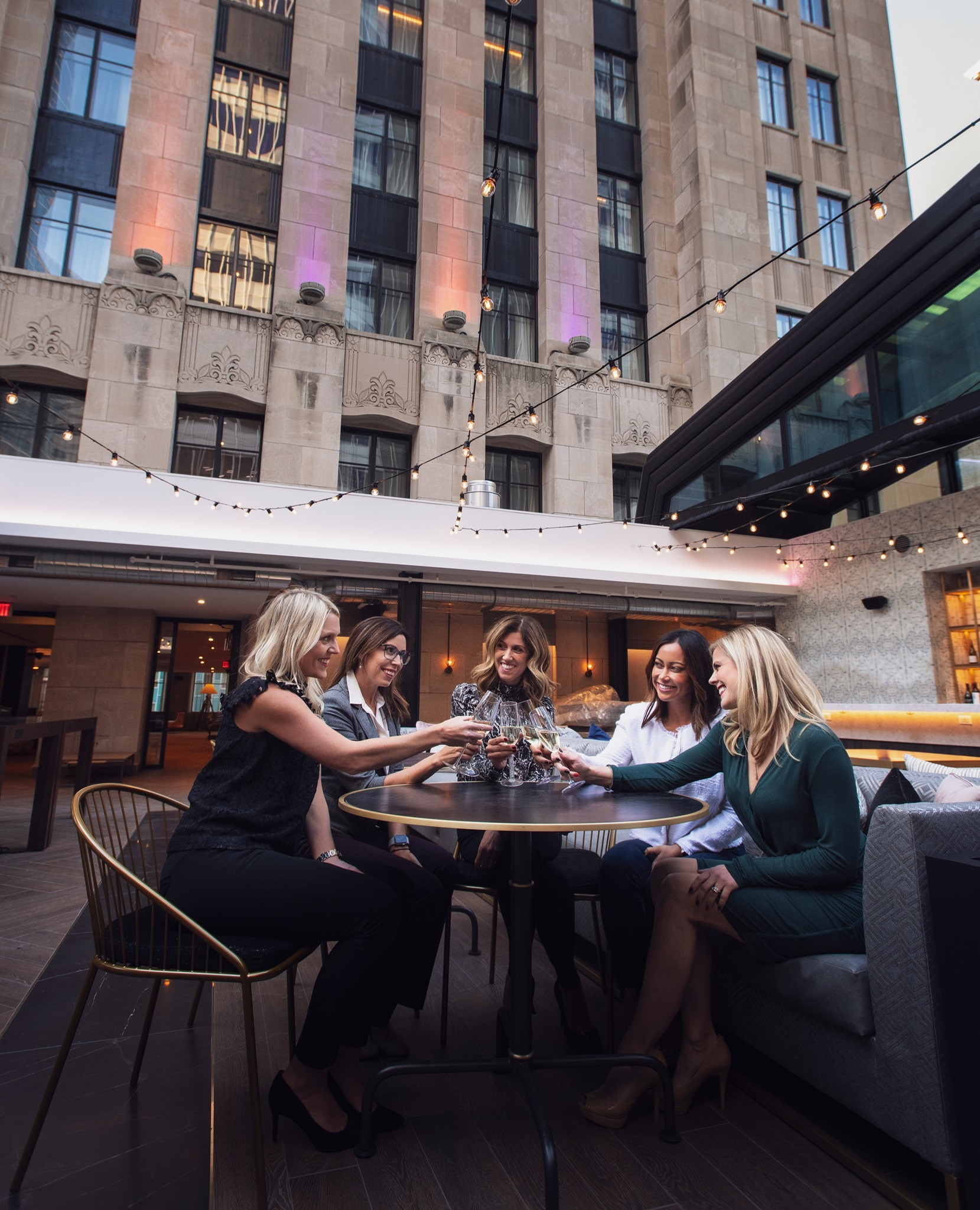 Four women sit around a table, clinking glasses. The black table is outside on The Rand Tower's rooftop terrace with dimly lit bistro lights strung above the table. In the background is the new hotel tower.