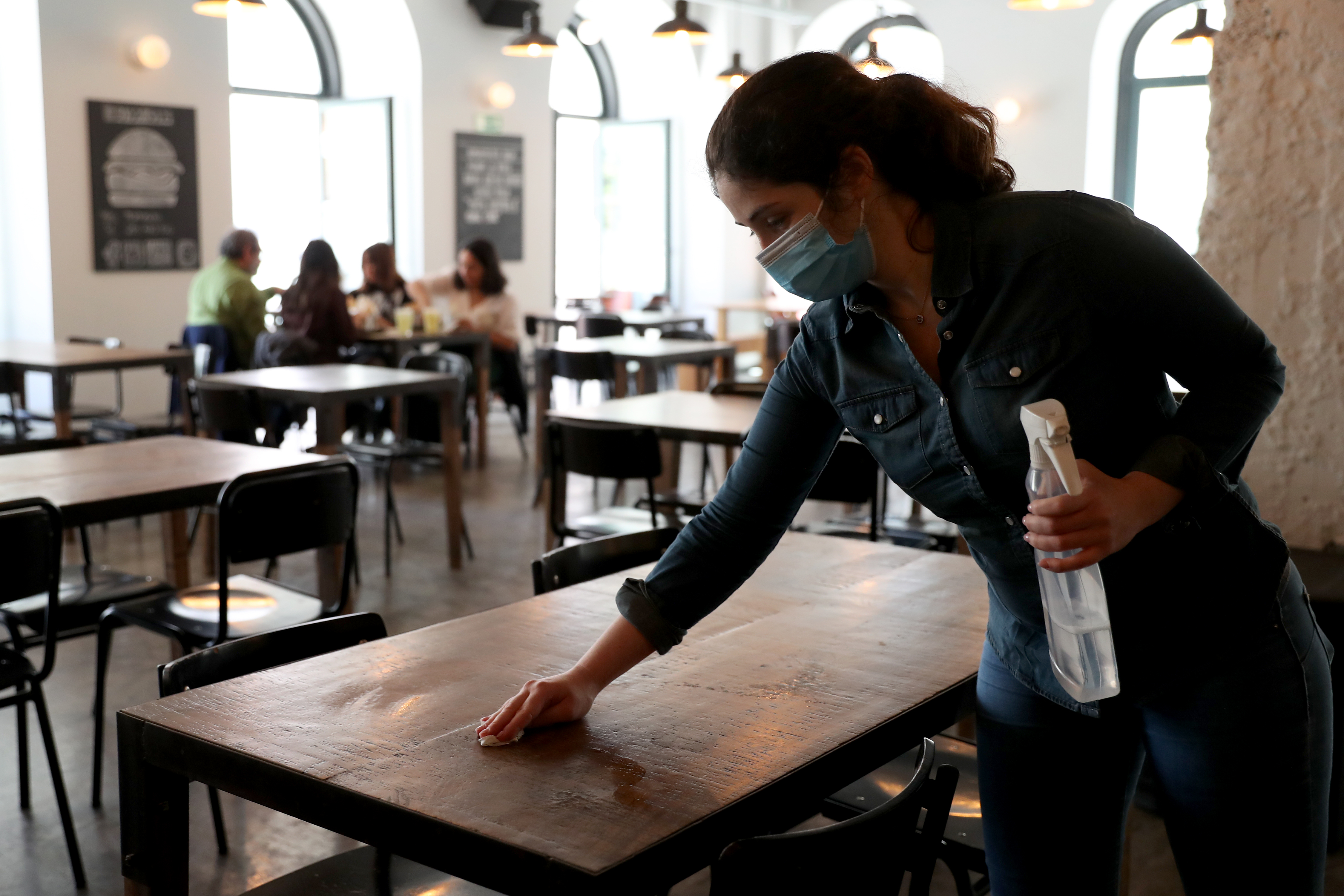 A woman wearing a mask wipes off a table inside a restaurant.