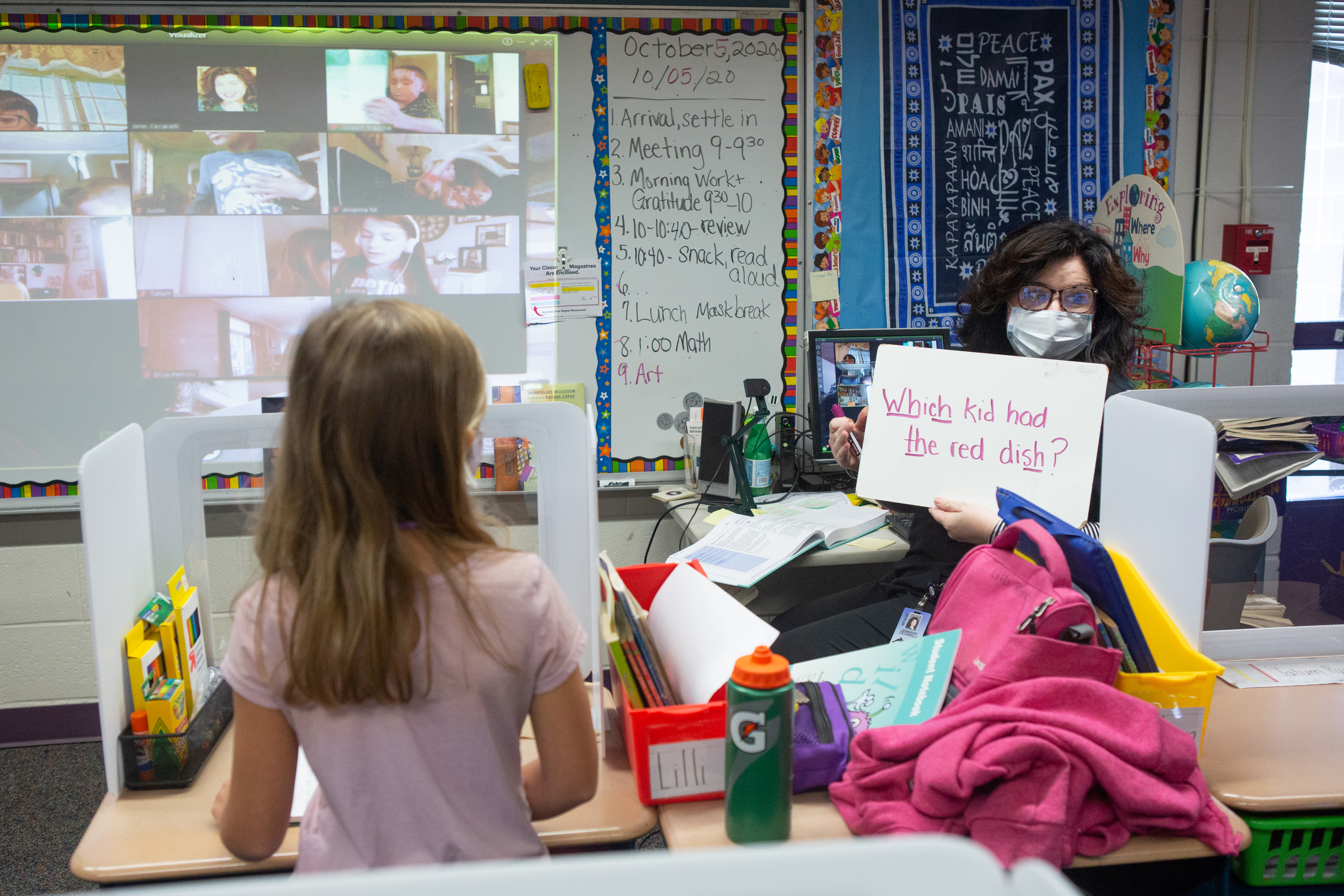 """Second grade teacher Mrs. Cecarelli, wearing a mask, holds up a placard with the words, """"Which kid had the red dish"""" with the digraphs Wh, ch, th and sh underlined.  A girl in a pink top stands in the foreground in a classroom, while a board with a projection of students participating remotely is in the background, at Wesley Elementary School in Middletown, CT, October 5, 2020."""
