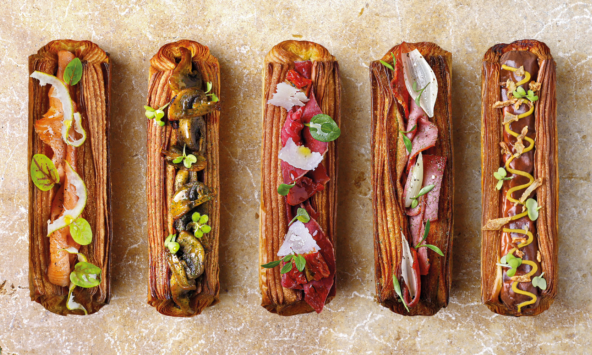 A quartet of pastry eclairs topped with delicately cut fruits, herbs, and flowers, seen from above