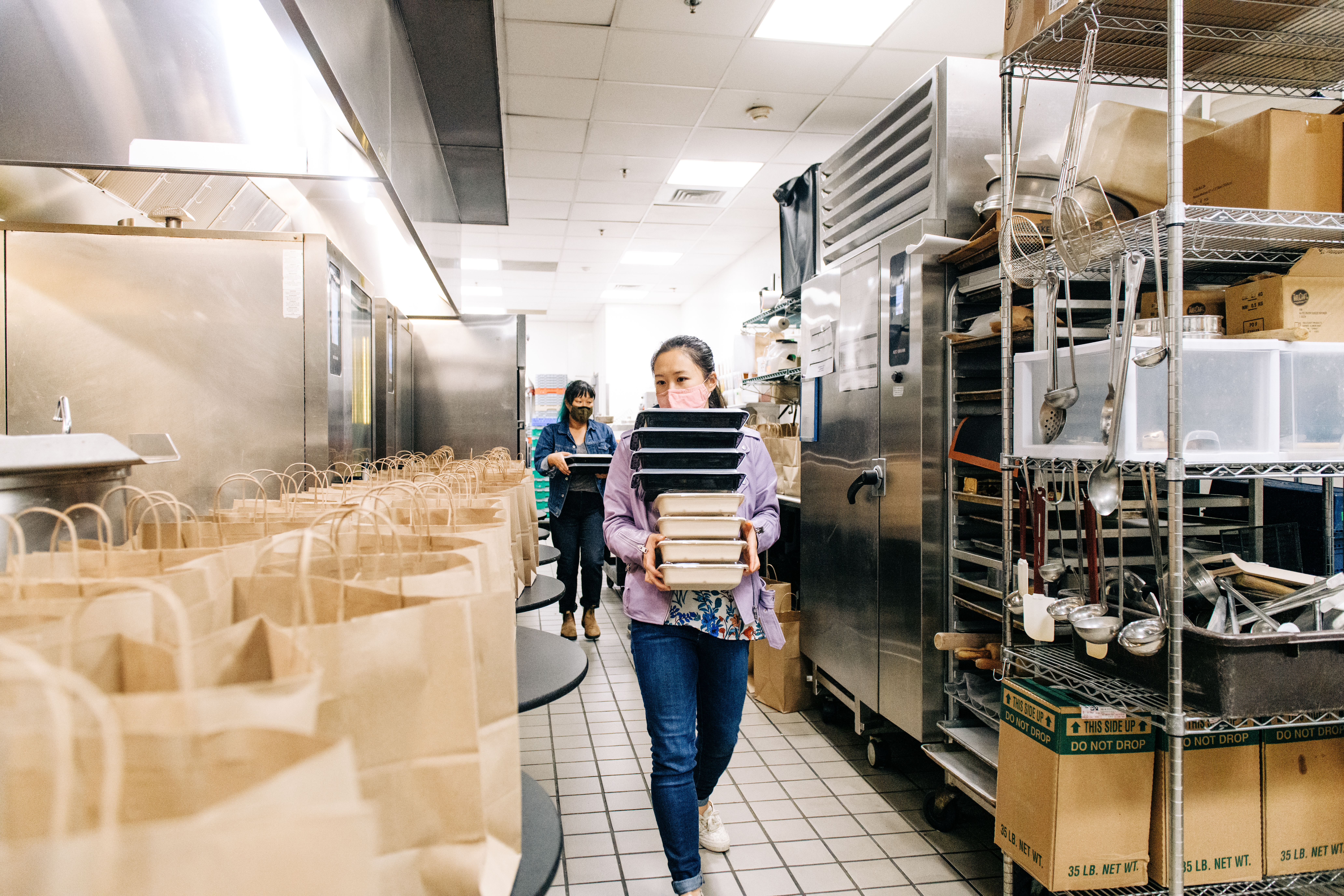 Chefs Stopping AAPI Hate volunteers Lillie Zheng and Helen Choe carry stacks of takeout boxes next to a table prepared with bags inside the kitchen at Moon Rabbit in D.C,