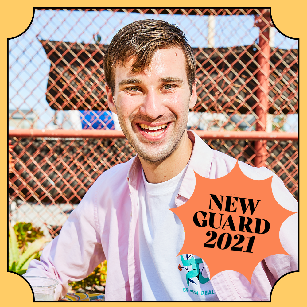 """A man smiles for the camera, a badge superimposed on the photo reads """"New Guard 2021"""""""