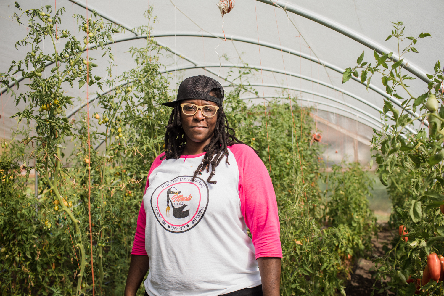 A woman stands in a greenhouse
