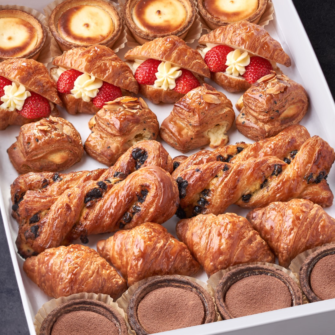 Croissants on a tray, some stuffed with strawberries and cream