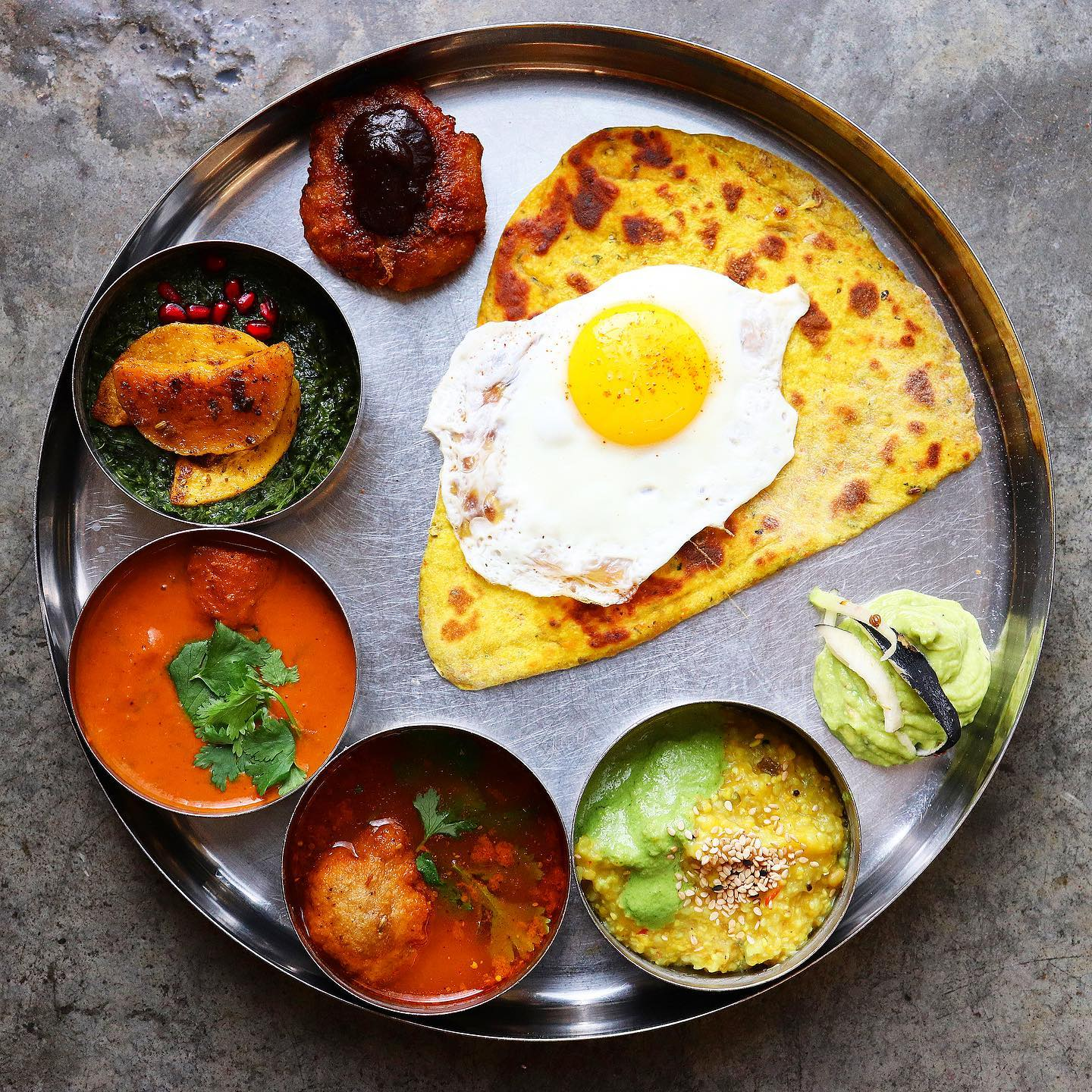 a morning thali spread with crispy carrot paratha and a fried egg