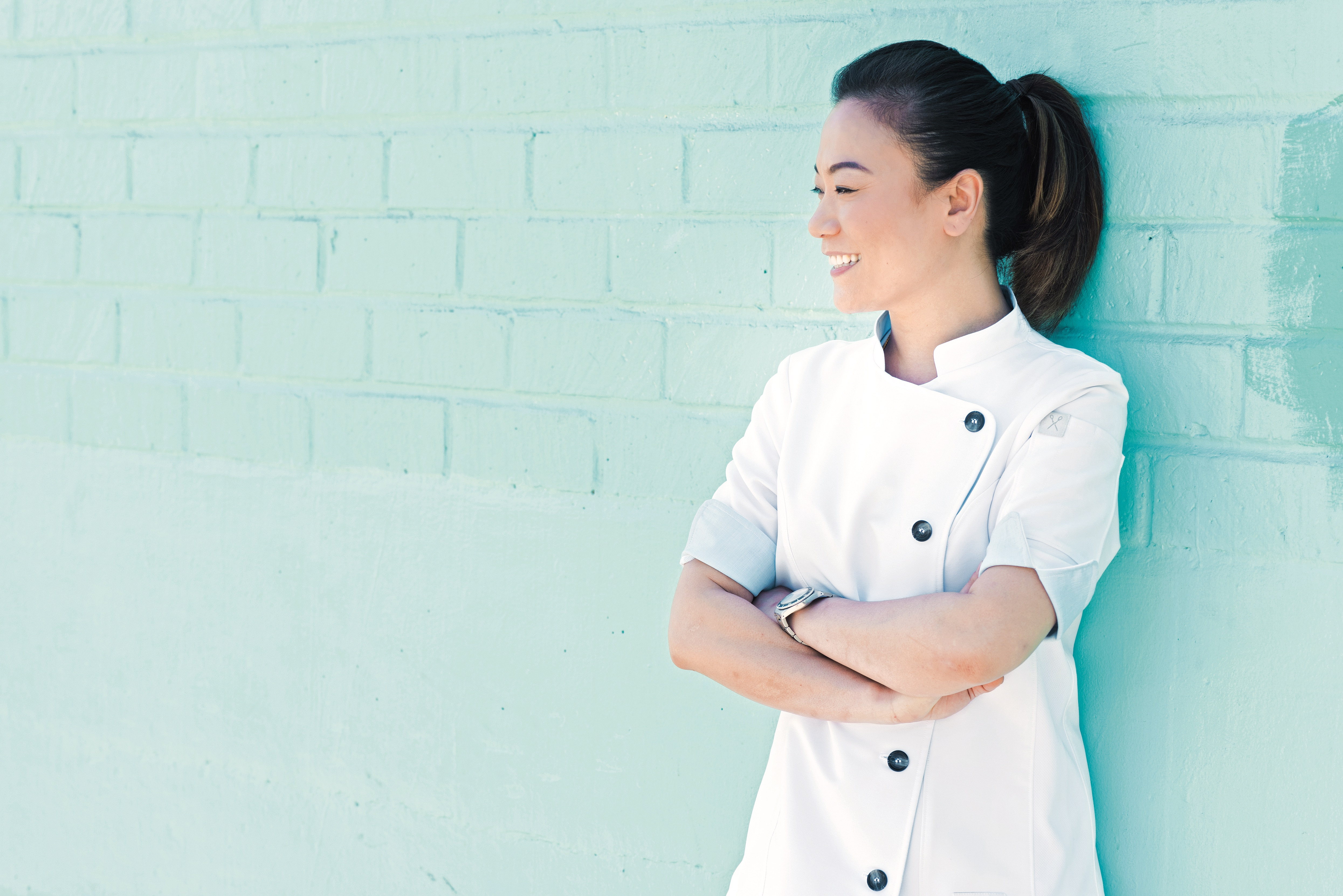 A chef in whites stands, arms crossed, next to a teal wall.